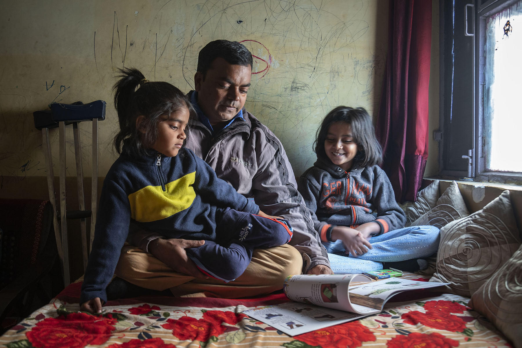 Ameer sitting crosslegged on a bed with his two daughters Areeba and Aayat on either side, turning the pages of a children's book. The wall behind them is covered with childish scribbles.