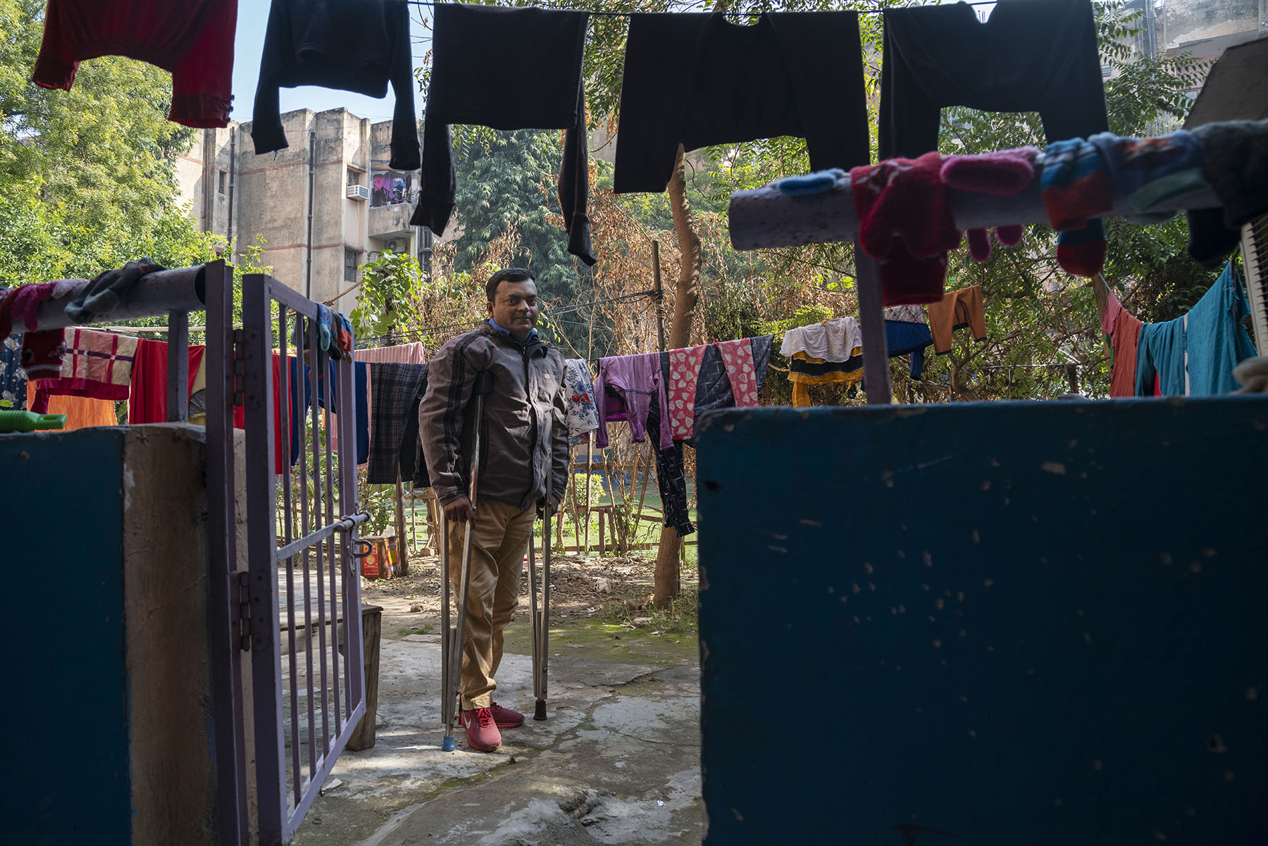 Ameer with his crutches standing outside an open gate, surrounded by washed clothes hanging on clotheslines