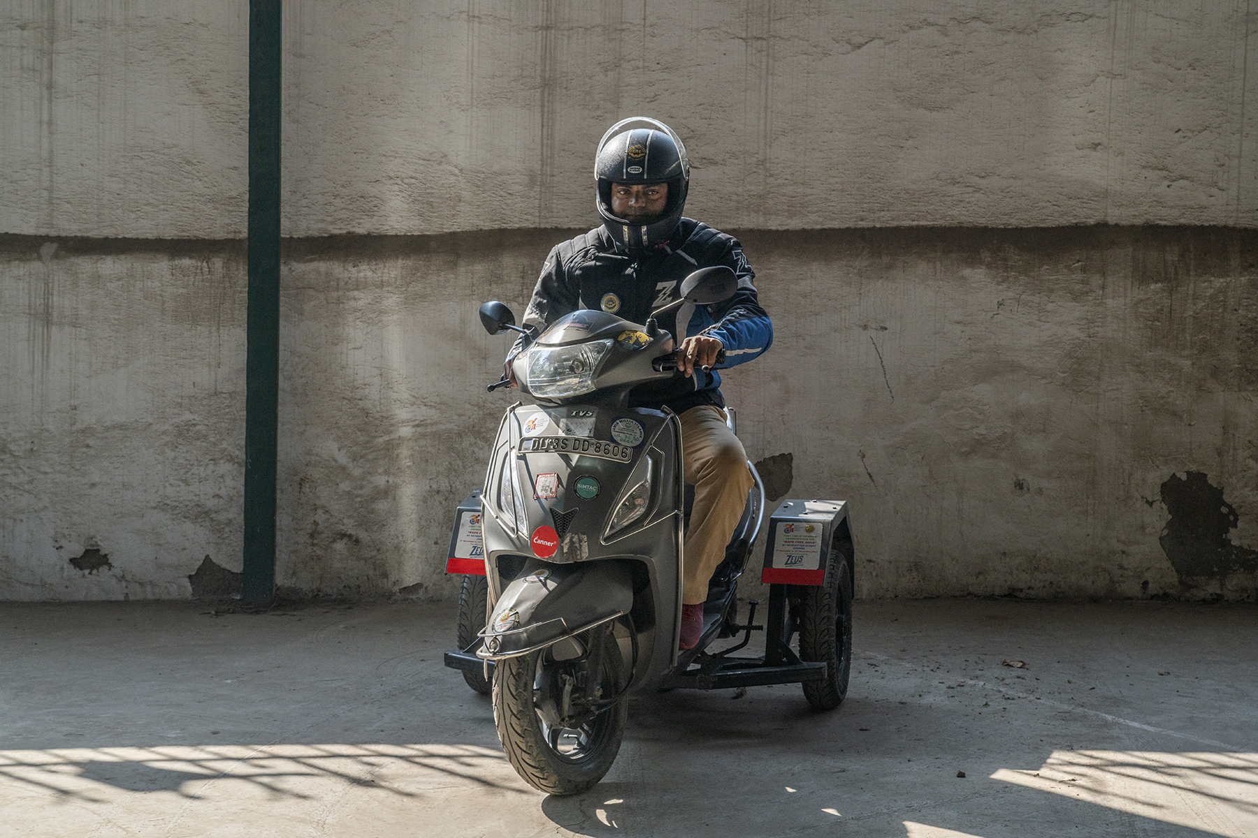 Ameer astride his black retrofitted scooter, wearing a full-face helmet and black jacket