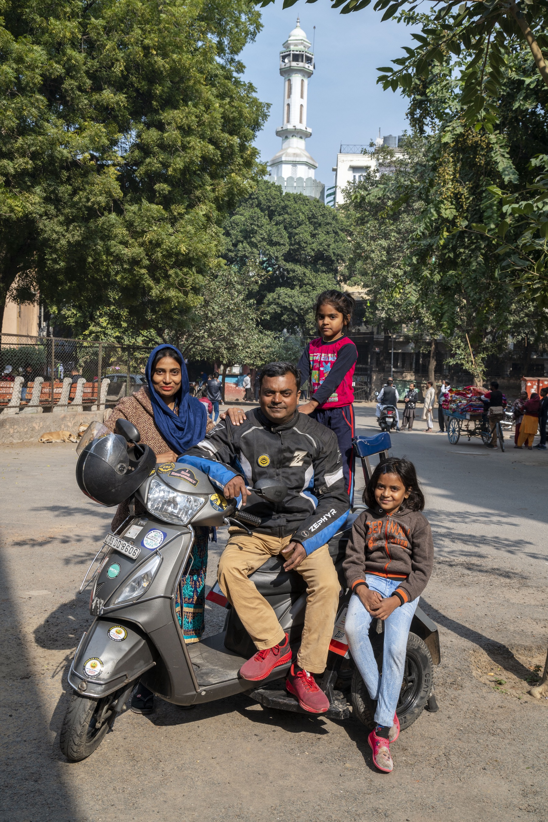 Ameer sits on his retrofitted scooter parked on a street. His wife Kailash stands to the left, her hand on his shoulder. Their older daughter Areeba stands behind him and the younger Aayat sits to the right. Behind them, a minaret peeps through the trees.