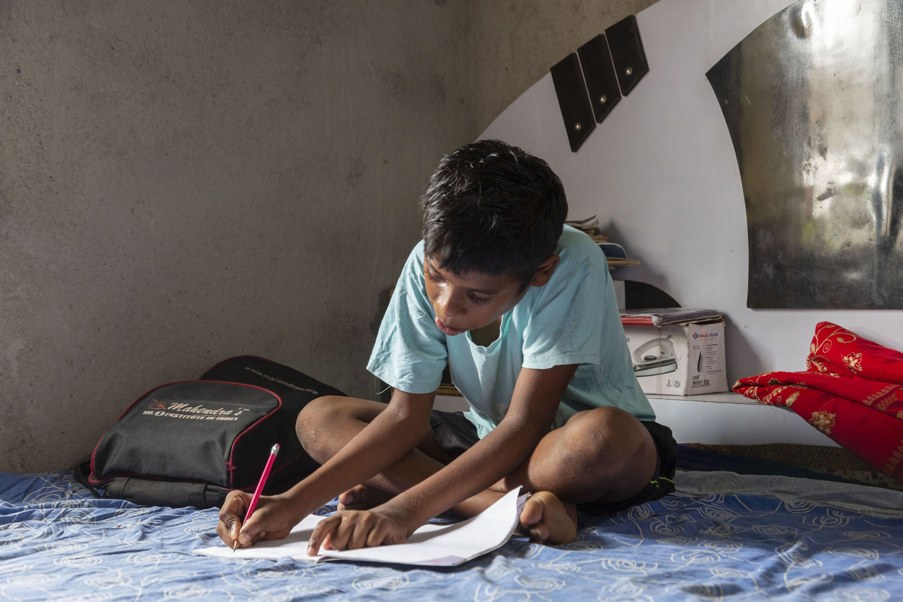 Aman in a light blue half-sleeved T-shirt sits cross-legged on a bed, head bent over an open notebook. He is writing with a pink-coloured lead pencil with an eraser tip. A black schoolbag lies next to him. The bed is covered with a light blue sheet.