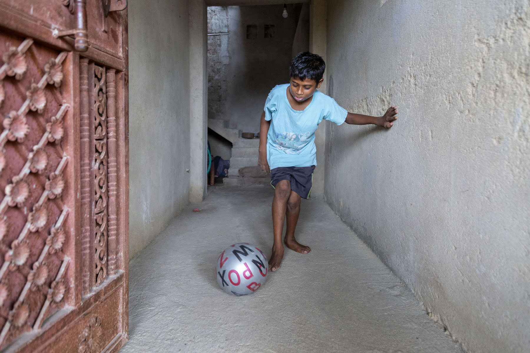 Aman in light blue half-sleeved T-shirt and navy blue shorts is kicking a plastic ball in a corridor. The walls of the corridor have not been plastered and the floor is unfinished. The silvery-grey ball has capital letters of the alphabet on it, in red and black.