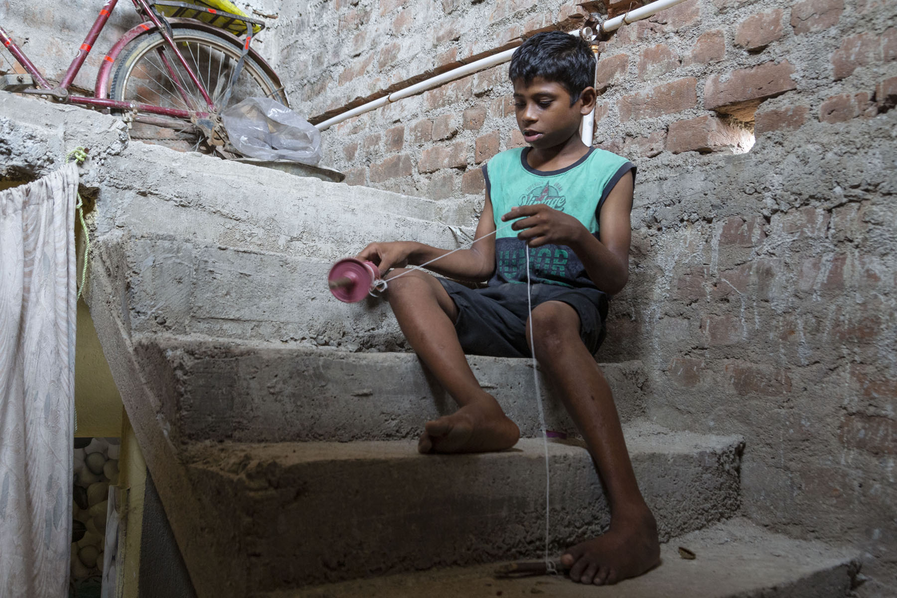 Aman, in blue sleeveless T-shirt and navy blue shorts, sits on a step of a rough concrete stairway. The wall next to it is also unfinished, with bricks and cement showing. Aman holds a plastic spool (used for kite flying) in his right hand and the spool's string with his left. The end of the string is tied to a wooden stick resting on the step below him.