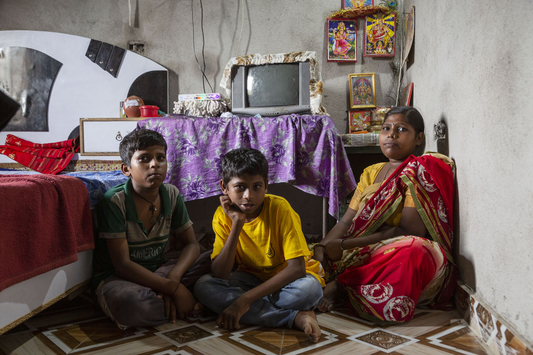 Sitting cross-legged on the floor of a small room with bare concrete walls are (from left to right), Aman's brother Ankit Kumar Mahto (12), Aman, and their mother Sanu Devi (33). Ankit wears a green and grey T-shirt and grey pants; Aman wears a yellow T-shirt and blue jeans; Sanu wears a red sari and yellow blouse. The floor is paved with tiles in a design of brown and white squares. To their left is a cot covered with a red blanket. Behind them, an old TV sits on top of a table covered with a cloth in a violet and grey pattern. To the right of the table is a stand with framed pictures of many gods and goddesses.