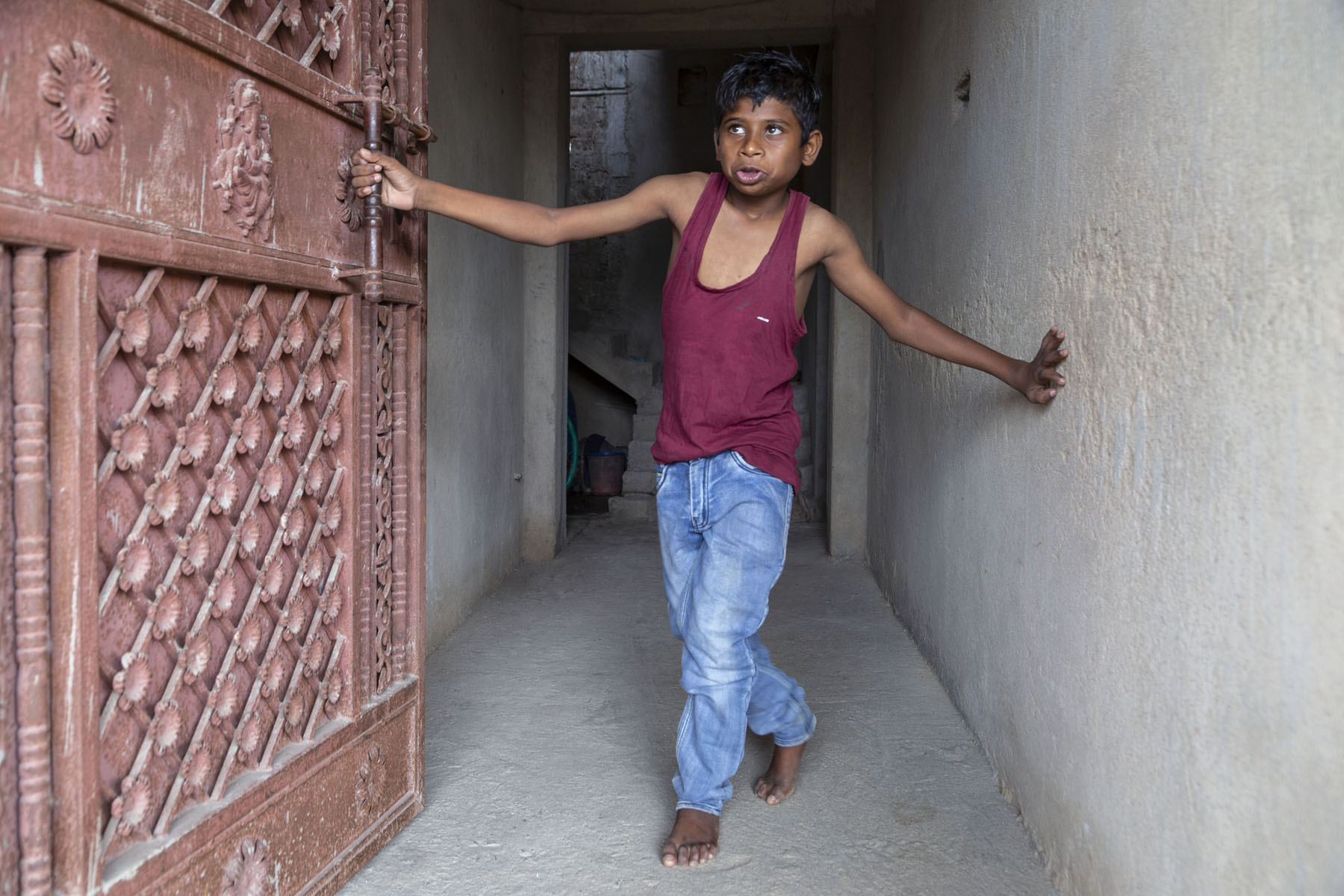 Aman Kumar Mahto, in maroon vest and light blue jeans, stands next to an open, decoratively carved door. His right hand holds the door handle and his left hand touches the wall.
