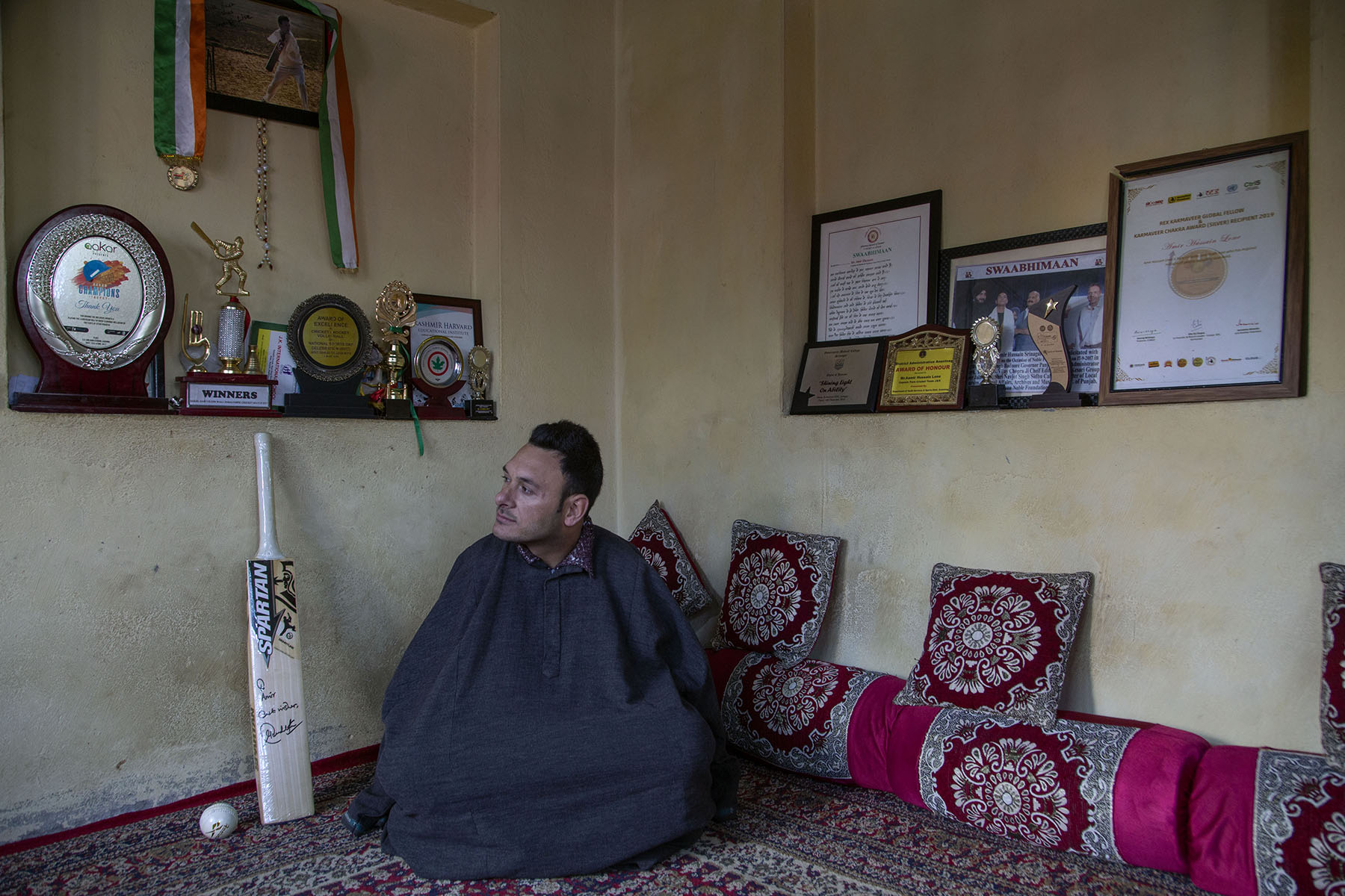 Amir enveloped in a grey pheran sits on a rug in a room that displays several framed awards and certificates, and medals hanging from ribbons. To his left is a white, autographed cricket bat propped up against the cream wall, next to a white cricket ball.