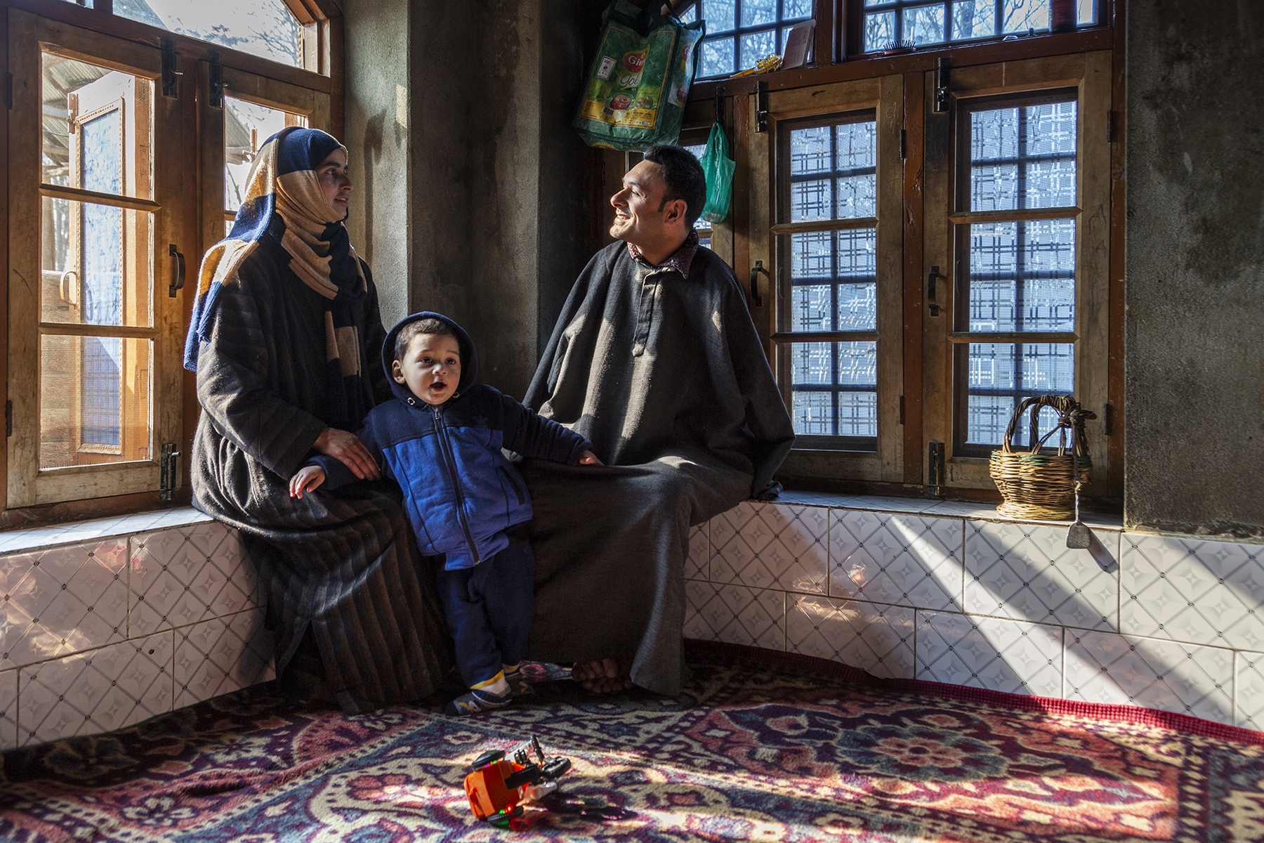 Amir with his family in a corner of a room with two large windows at right angles to each other. Amir is sitting on the sill of the window on the right, smiling and facing his wife Shokhi sitting on the other window sill. Their son Imaad is standing between them. The sun is shining on Amir's face through the glass panes. He wears an ankle-length grey pheran, Shokhi is in a striped pheran and has a scarf wrapped around her head and shoulders, and Imaad wears a navy blue jacket with a hood and matching pants.
