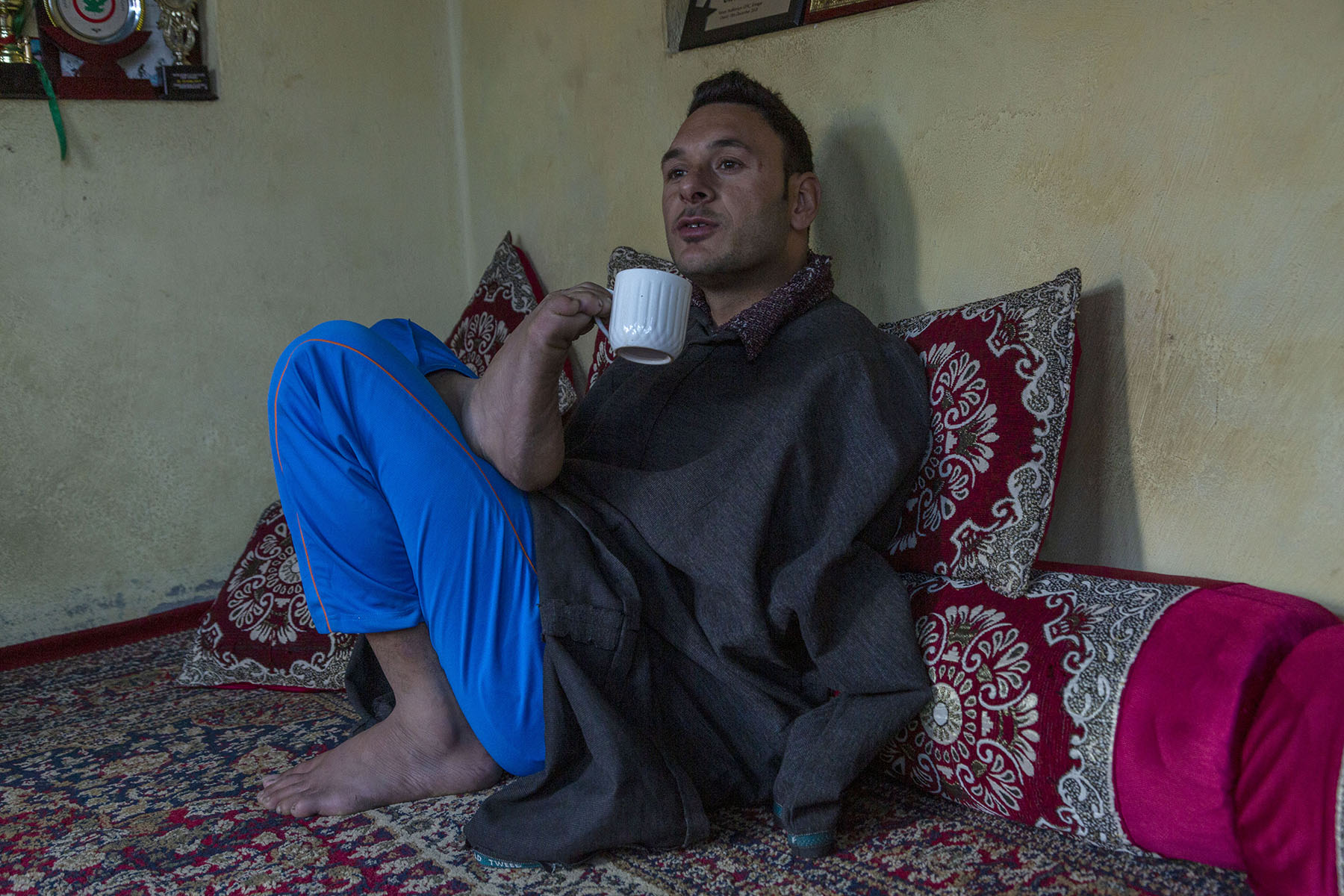 Amir sits on a rug in a room, leaning back against a bolster and cushions, holding a porcelain cup with his right foot. He wears a charcoal grey woollen pheran (Kashmiri gown) over blue pants. The rug and cushions have a similar red and grey floral pattern.