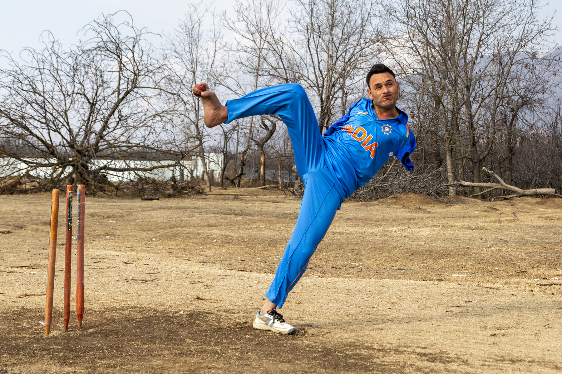 Amir Hussain Lone in blue cricket jersey and pants is bowling with his right leg raised high up in the air while his body is tilted to the right. The ground is a flat but rough surface of brownish soil. To the left are three orange cricket stumps and behind him, a row of spindly, leafless trees.