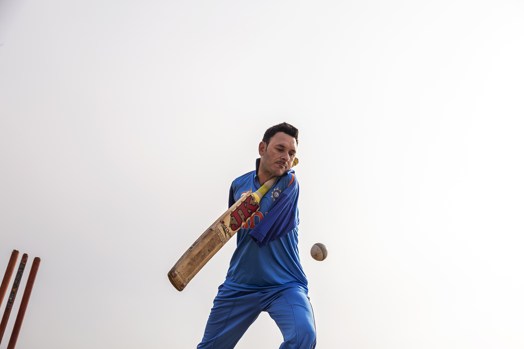 Amir in blue cricketing uniform is framed against a stark white sky, caught in the act of batting. The cricket bat is at an angle, tucked under his chin, and the ball captured by the camera is frozen at waist level. Three stumps jut out from the bottom left corner of the frame.