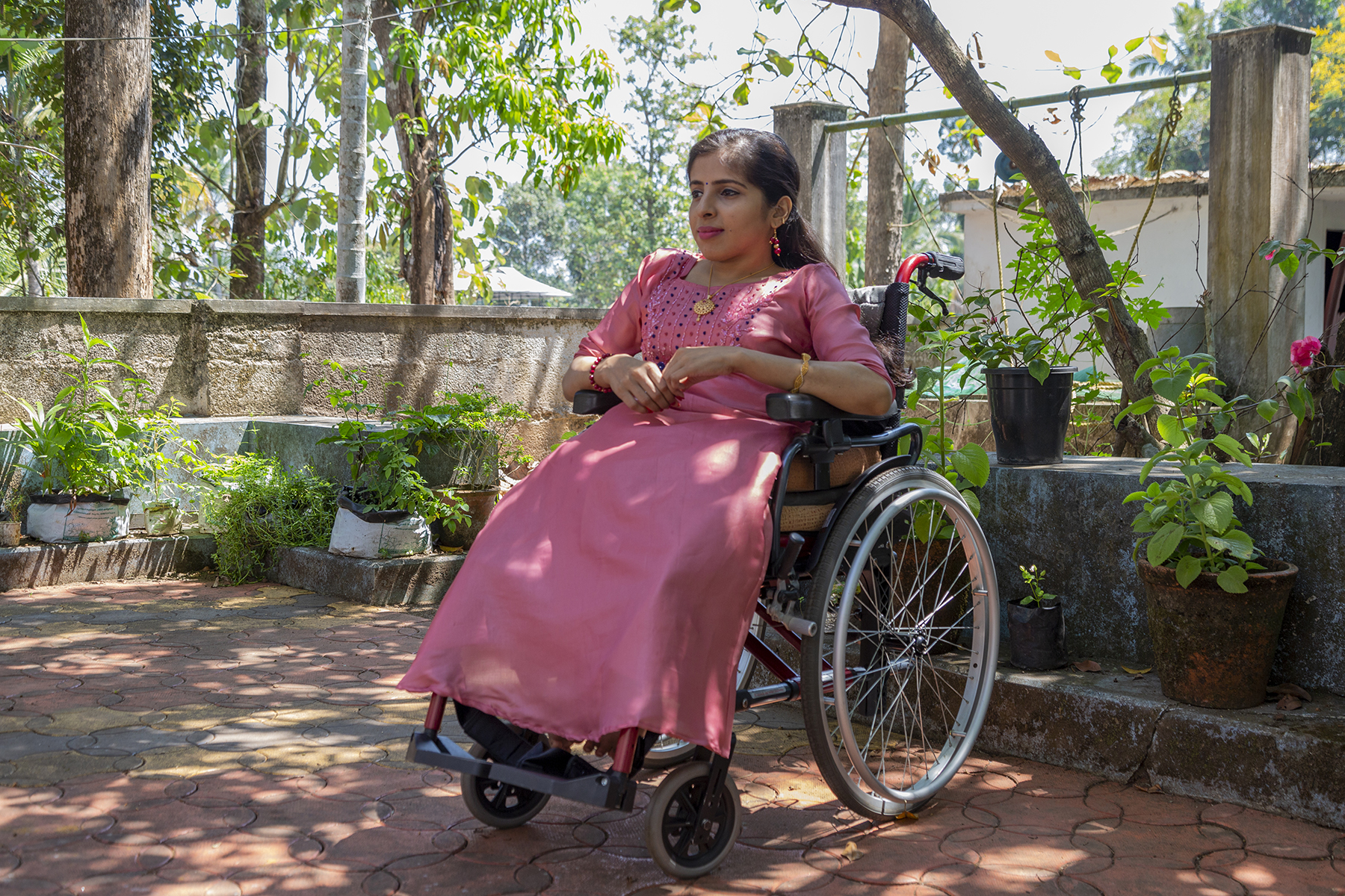 Anju Rani in a peach-coloured kameez with half sleeves and embroidered front panel sits in her wheelchair in the garden. Her long straight hair is tied back with a side parting and she wears dangling earrings and a gold chain with a circular gold pendant. The ground is paved with tiles. Behind her are flower pots on a low parapet wall. Behind the wall, the presence of a well is indicated by two rectangular concrete pillars spanned by an iron rod from which a pulley and coir rope are dangling.