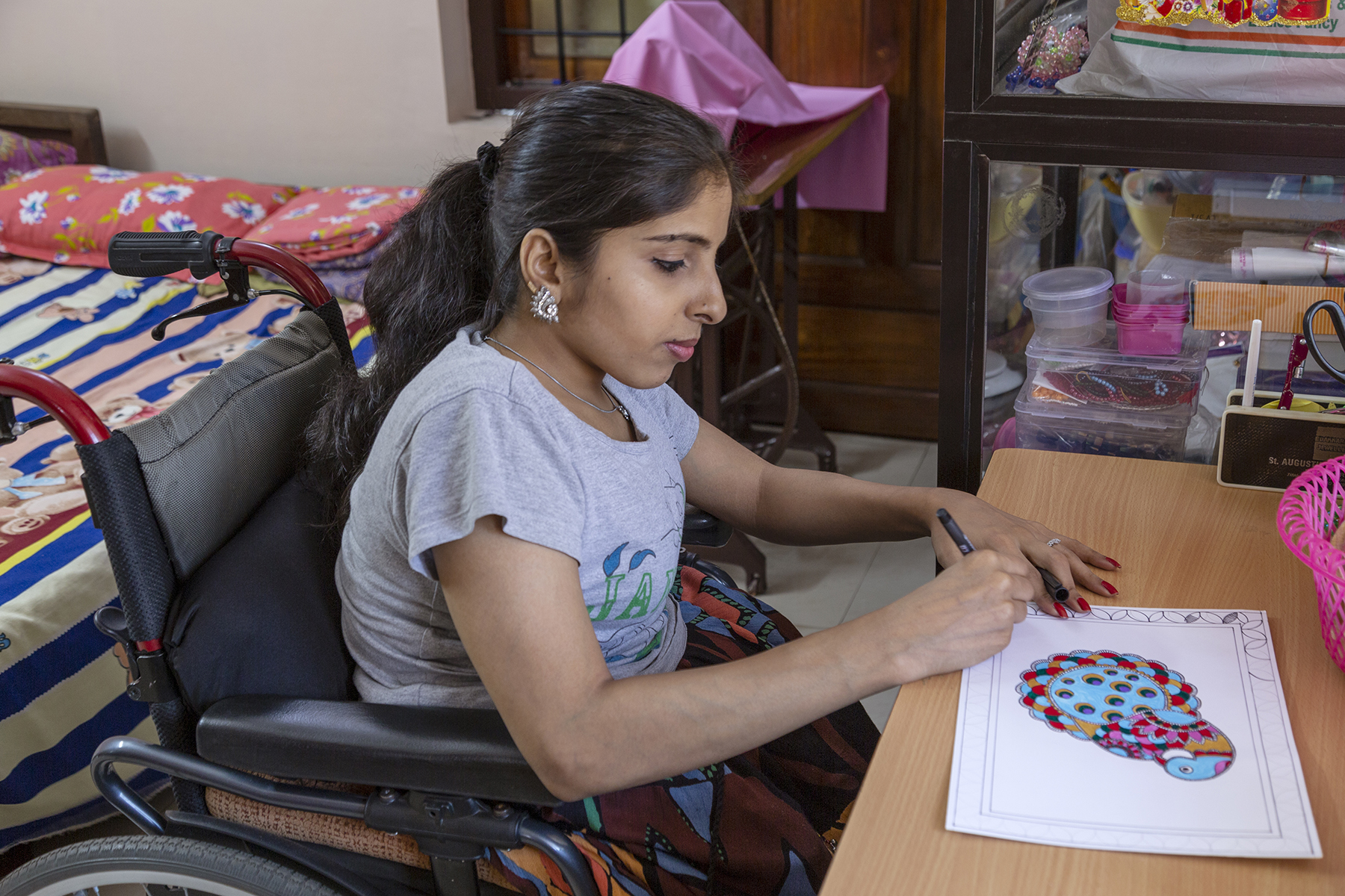Anju Rani sits in her wheelchair behind a table with a beige wooden finish. She wears a grey short-sleeved T-shirt, a multi-coloured skirt, a silver chain and silver ear-studs. She holds a black pen to a sheet of paper that has the drawing of a stylised parrot painted in red, blue, orange and pink. She is outlining a decorative black border for the painting.