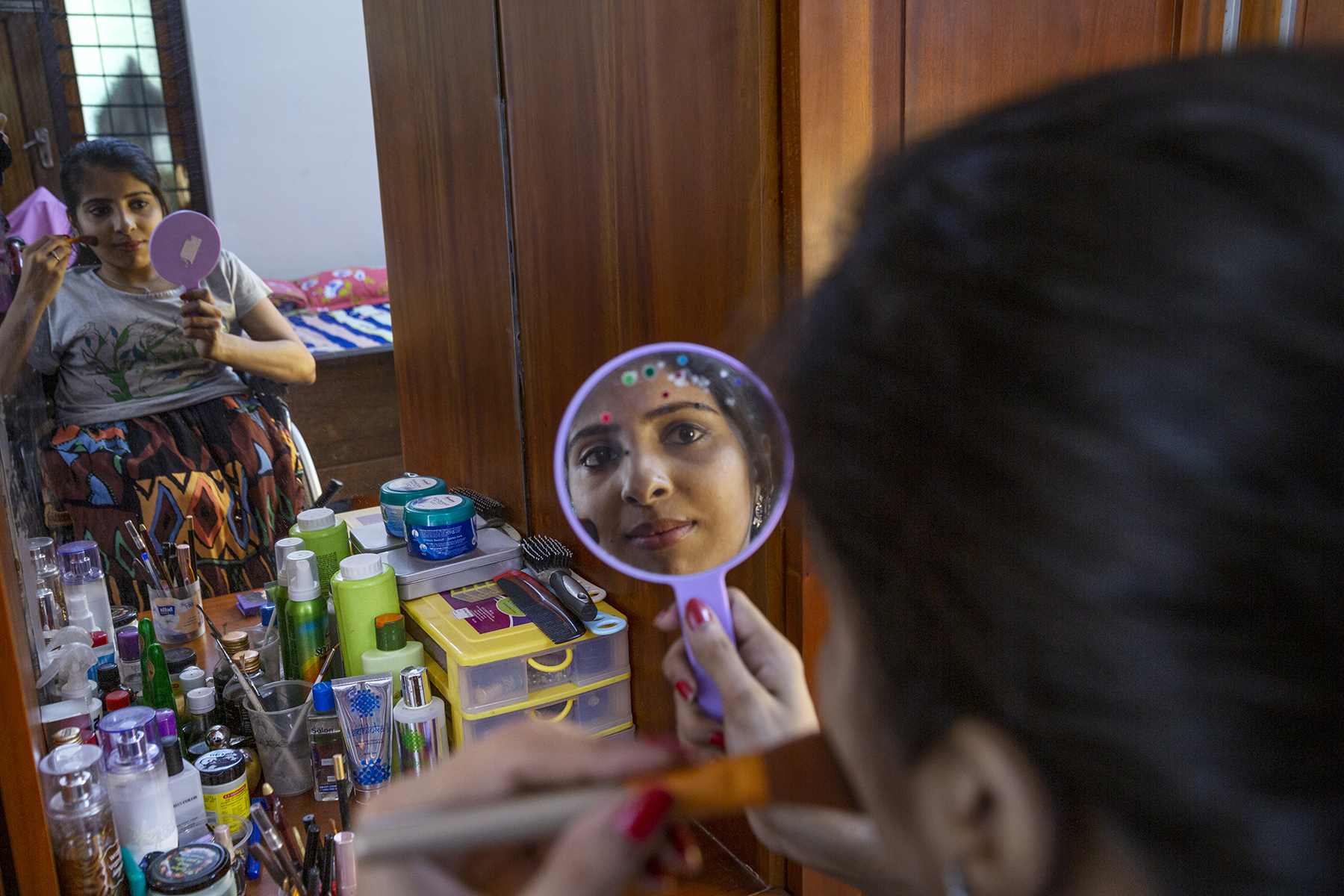 Anju Rani in grey half-sleeved T-shirt and multi-coloured skirt is reflected in a dressing table mirror. She is applying rouge on one cheek with a brush while holding a violet-framed hand mirror that reflects a close-up of her face. The dresser is crowded with cosmetics, a hair brush and a comb.