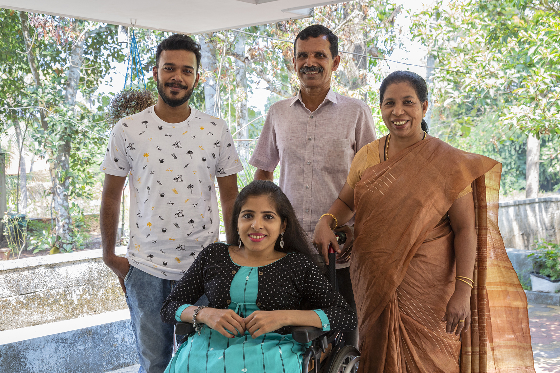 Anju Rani poses outdoors in her wheelchair with her family. Her hair is loose, she has red lipstick on, and she wears silver dangling earrings and a silver bracelet. A mock, full-sleeved, black waistcoat with white polka dots is stitched onto her sapphire blue kameez. Behind her (from left to right) are her brother Amal Joy (28) in blue jeans and white T-shirt, father Joy K.G. (61) in light pink shirt and dark trousers, and mother Jessy Joy (56) in a light brown sari and sandalwood-coloured blouse.