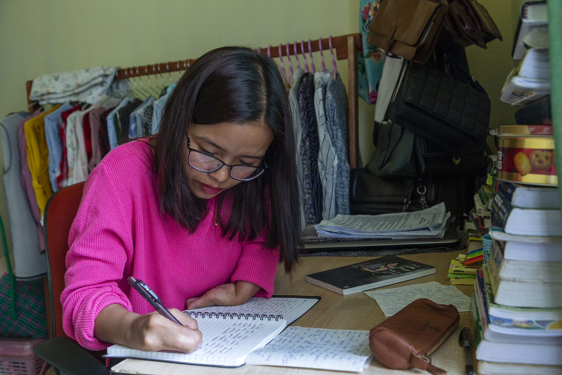 Ashe wearing spectacles and a shocking pink cardigan sits at a table, writing with a pen in a ruled notebook. Behind her is a clothes rack on which hangs a row of clothes hangers with feminine tops of many colours and patterns. The table is crowded with piles of books.