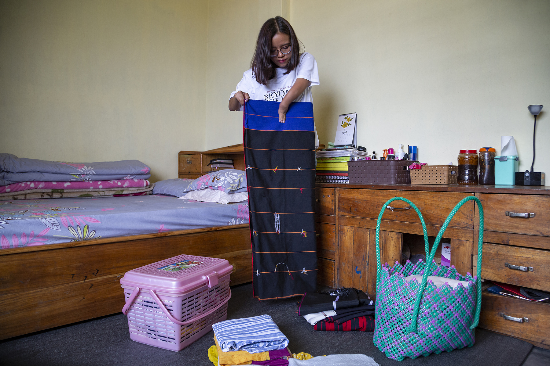 Ashe stands in her bedroom, vertically folding a typical Naga shawl worn by women. It is black, with a wide strip of royal blue at the top. Thin horizontal stripes of orange divide the shawl into 10 broad bands. To the left is a wooden cot with mattress covered in a pink and grey patterned bedsheet. To the right is a long wooden table with drawers. In front of her are two small piles of folded clothes, a pink plastic hamper with a lid, and a large plastic, woven, pink-and-green bag with long green handles.