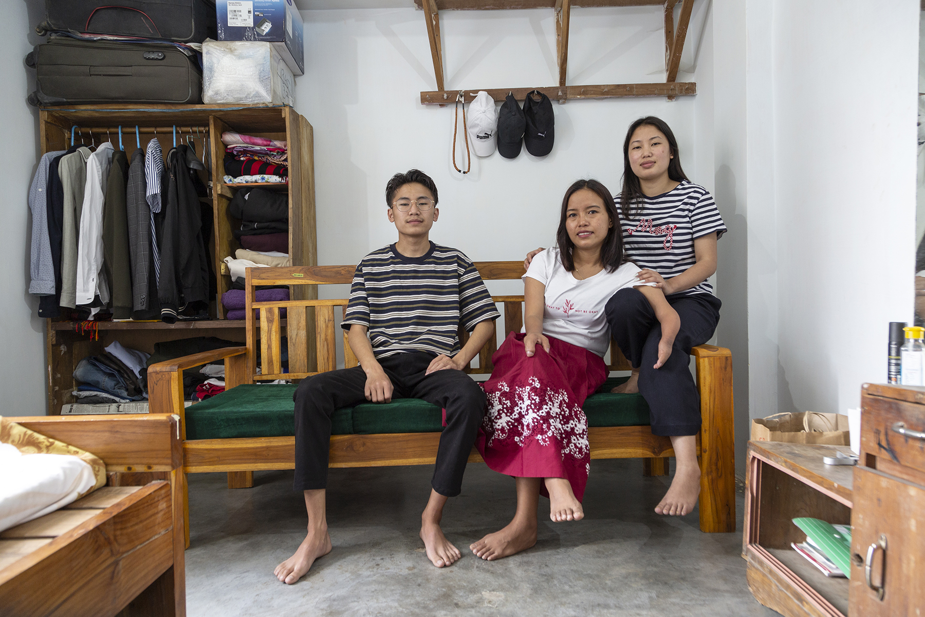 Ashe, her cousin-brother Itsa Muru (19) and cousin-sister Villa Muru (25) are seated on dark green cushions on a wooden settee. Itsa wears a T-shirt of horizontal black and white stripes and black pants and Villa wears the same combination except that the stripes on her T-shirt are narrower. Ashe sits between them in a white T-shirt and crimson skirt. All three are barefoot.