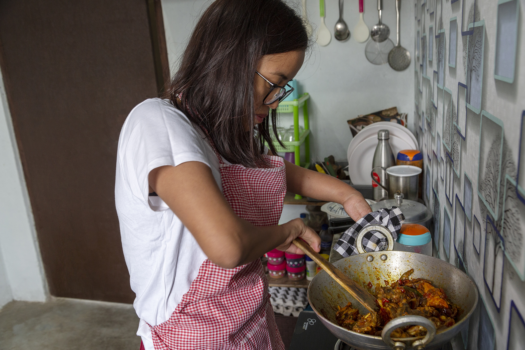 A side shot of Ashe cooking in her kitchen. She wears an apron of tiny red-and-white checks over a white T-shirt. She is stirring meat in an aluminium kadai on the stove with a wooden spatula. With a black-and-white chequered cloth in her left hand she supports the handle and side of the hot kadai.