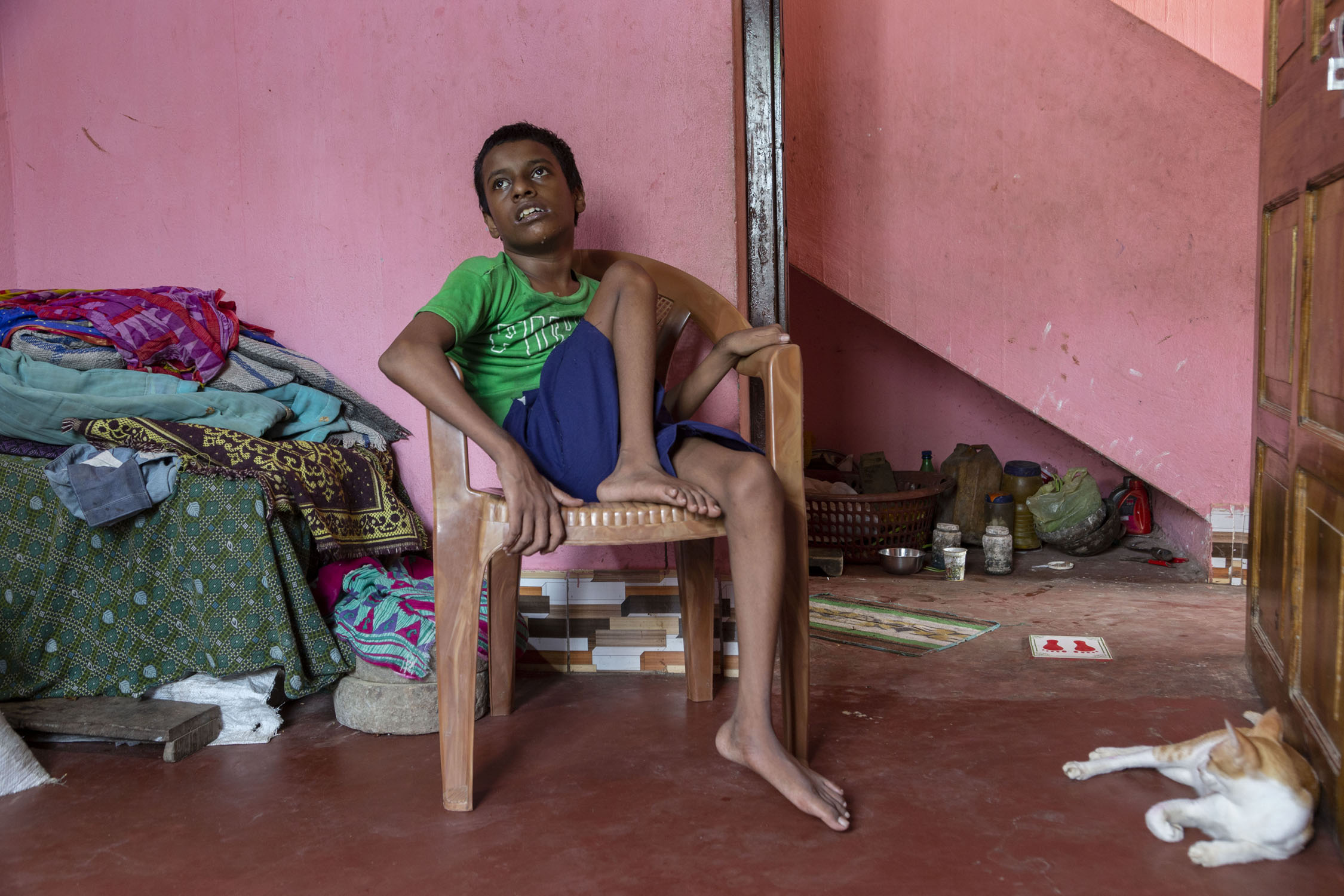 Asis Behera (14) wearing a green T-shirt and purple shorts sits in a light brown plastic chair. His left leg is extended and touches the floor. His right leg is folded at the knee and his right foot rests on the edge of the chair. To the right, a brown and white cat is lying on the floor next to an open door. The room has a red cement floor and bright pink walls.