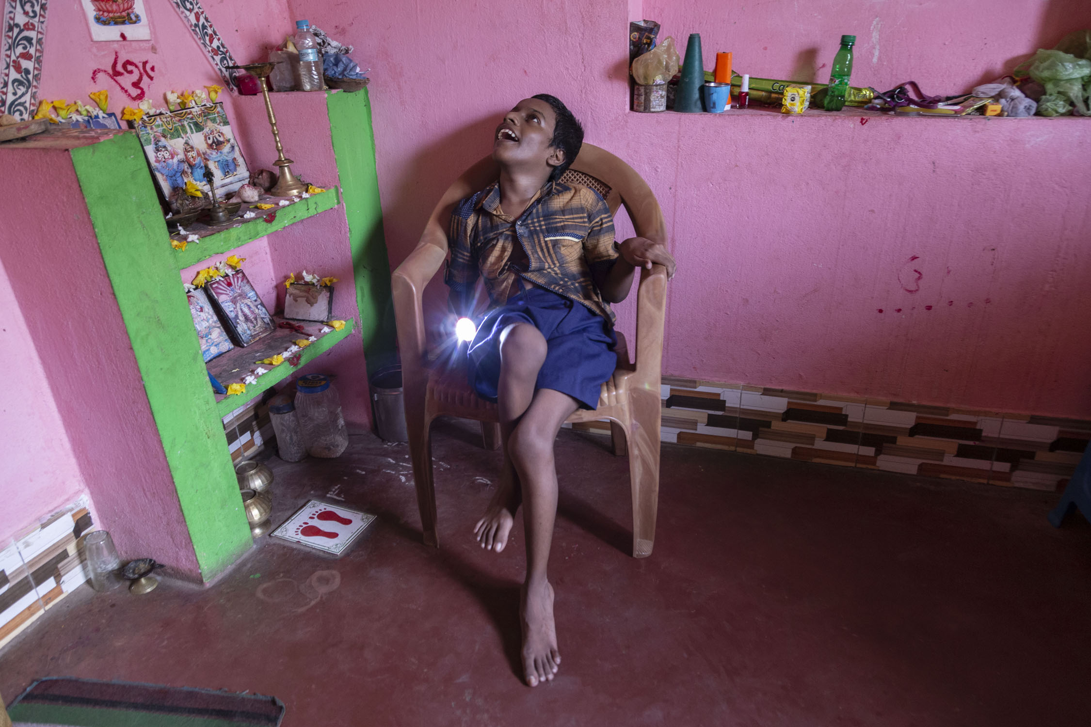 Asis, sitting in a light brown plastic chair and wearing a light brown and purple checked shirt with purple shorts, is looking upwards and smiling. The room has a red cement floor and bright pink walls. To the left is a cement shelf painted bright green and pink. There are devotional pictures and brass lamps on the two ledges of the shelf.