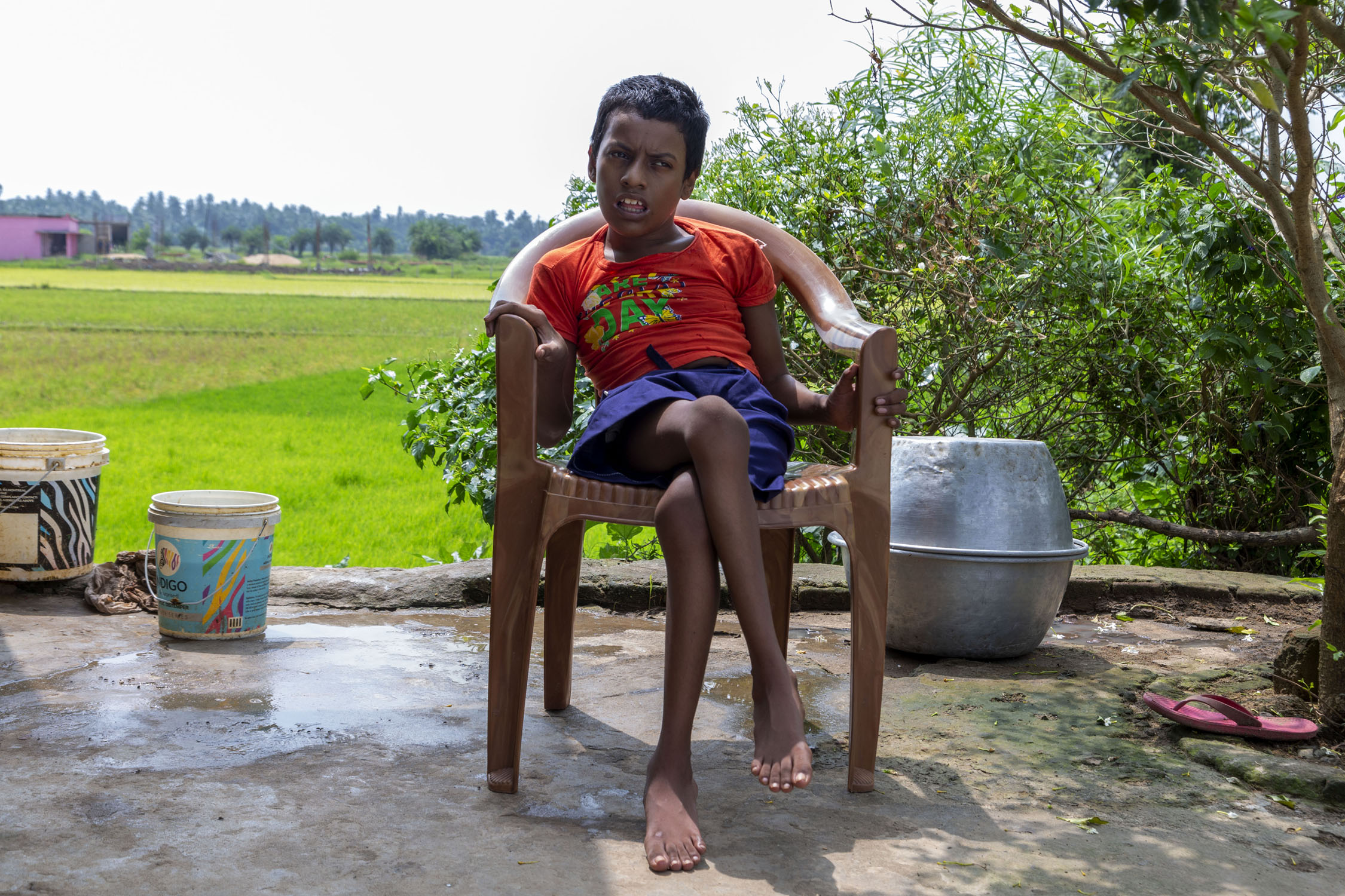 Asis wearing a red T-shirt and purple shorts sits outdoors in a light brown plastic chair. Paddy fields and a small tree are in the background. There are two plastic buckets to the left of the chair. To the right there are two large aluminium vessels, one placed upside down on top of the other to cover it.