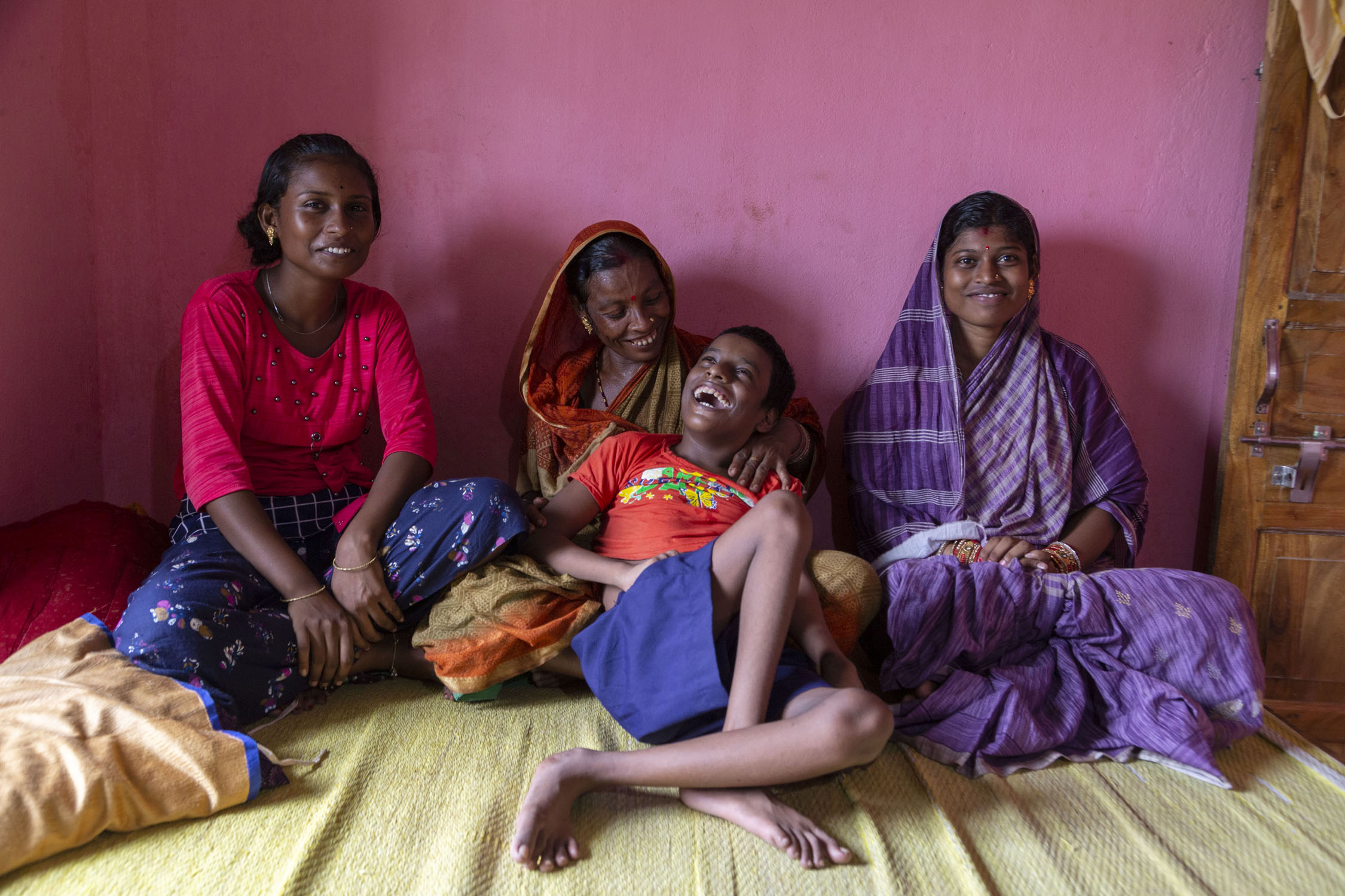Asis and his family sit on a cream mat on a wooden cot. From left to right: his older sister Liza Behera (15), mother Tanulata Behera (46) and eldest sister Lika Behera (19). Asis is leaning back against his mother's shoulder and laughing. The others are smiling broadly. Liza wears a magenta top and purple skirt printed with small pink, blue and white flowers. Tanulata wears a sari in a red, orange and brown design, with her pallu covering her head. Lika is dressed in a sari with a purple and white design and has draped her pallu over her head.