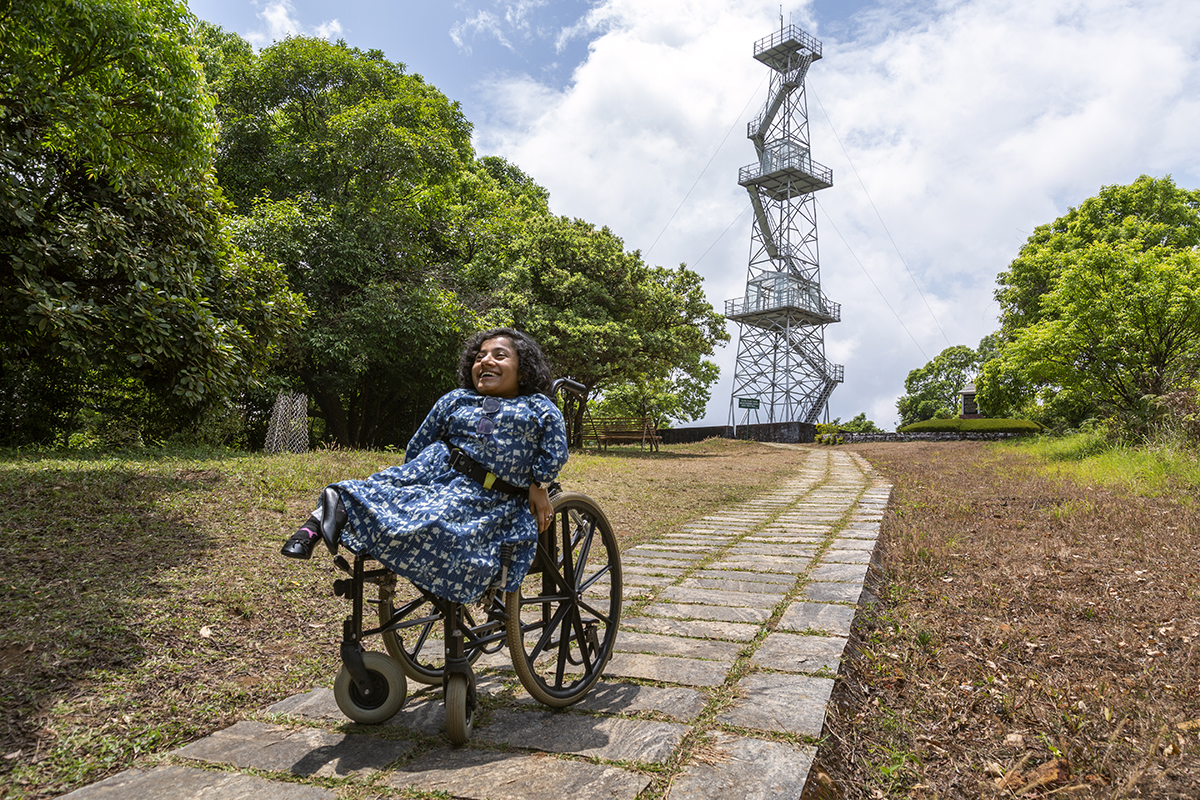 Dhanya in a blue-and-white dress is outdoors in her wheelchair, smiling broadly. The wheelchair is on a stone pathway that leads to a steel tower in the distance. On either side of the pathway there is a clearing edged with a row of tall trees that display lush green foliage.