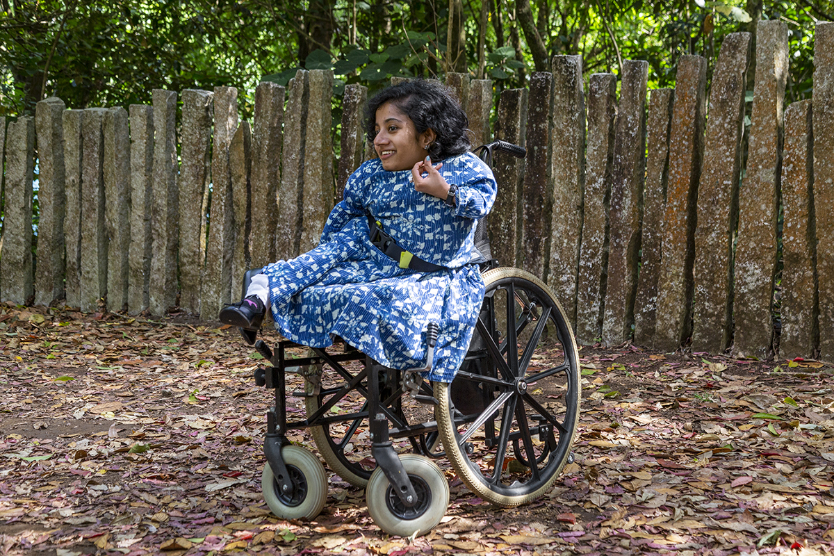 Dhanya Ravi, with shoulder-length wavy black hair, wearing a blue-and-white dress, sits in her wheelchair in Bandipur forest. The ground has a carpet of dry leaves. Behind her is a fence made of upright granite posts.