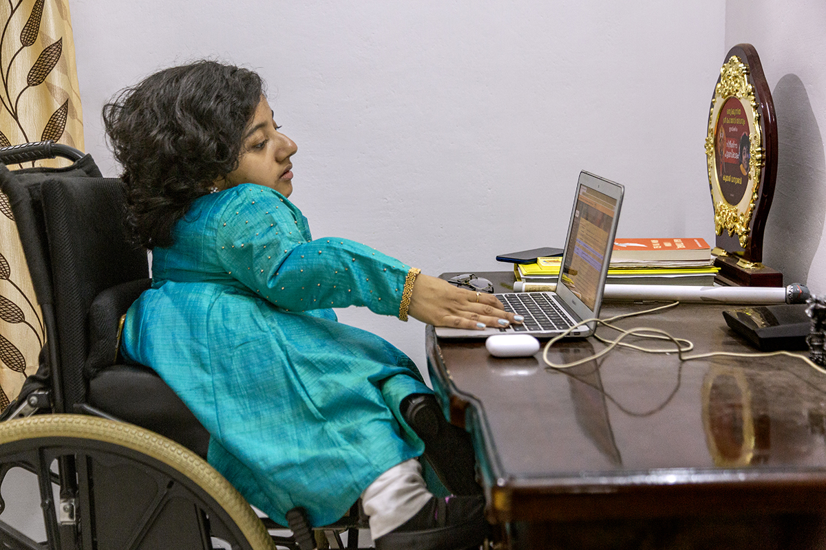 A side view of Dhanya in her wheelchair at a polished wooden desk, gazing into a laptop. She wears a full-sleeved copper-sulphate blue kameez and the edge of her white salwar peeps out below it. The fingers of her right hand, wearing pale blue nail polish, rest on the keyboard. On the table are a wood-and-metal trophy and a few books.