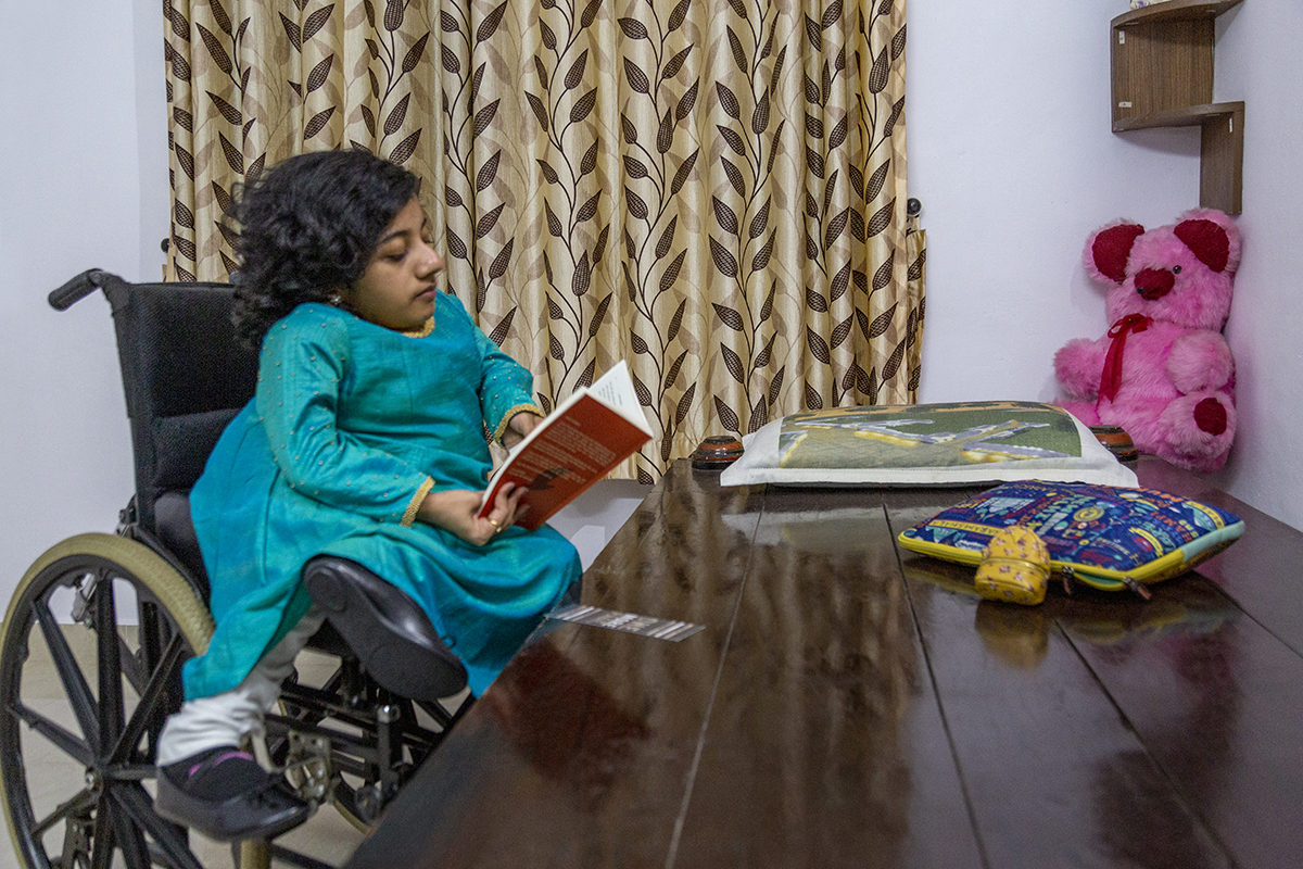 Dhanya in blue kameez and white salwar sits in her wheelchair, with both her feet, clad in black shoes, jutting out to one side. She is seated beside a highly polished wooden cot, reading a book. On the cot are two thin cushions and at the far right corner, a pink teddy bear sits propped up against the wall.
