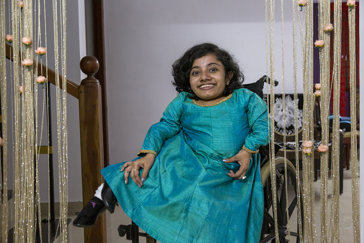 Dhanya wearing blue kameez, white salwar and a broad smile is facing us in her wheelchair next to the foot of a wooden stairway. Hanging vertically on either side of her like curtains are silvery strands studded with peach-coloured artificial roses.