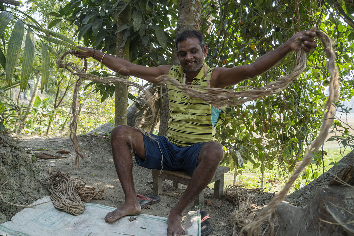 Gobinda Majumdar, in shorts and a striped sleeveless T-shirt, sits on a stool under a tree, jute yarn stretched across his widespread arms. On the ground next to his right foot is a hank of rope he has made from the yarn.