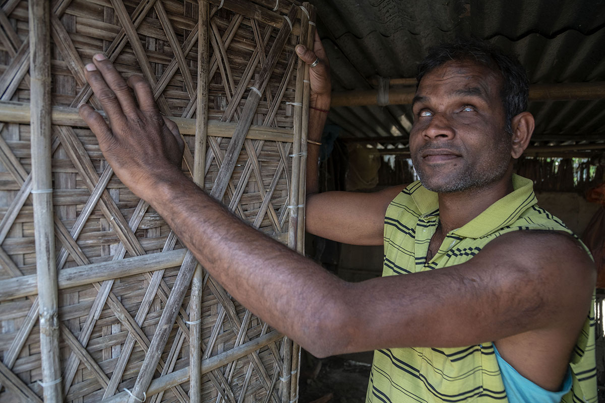Gobinda stands facing left, his hands supporting an upright bamboo cane door he has manufactured