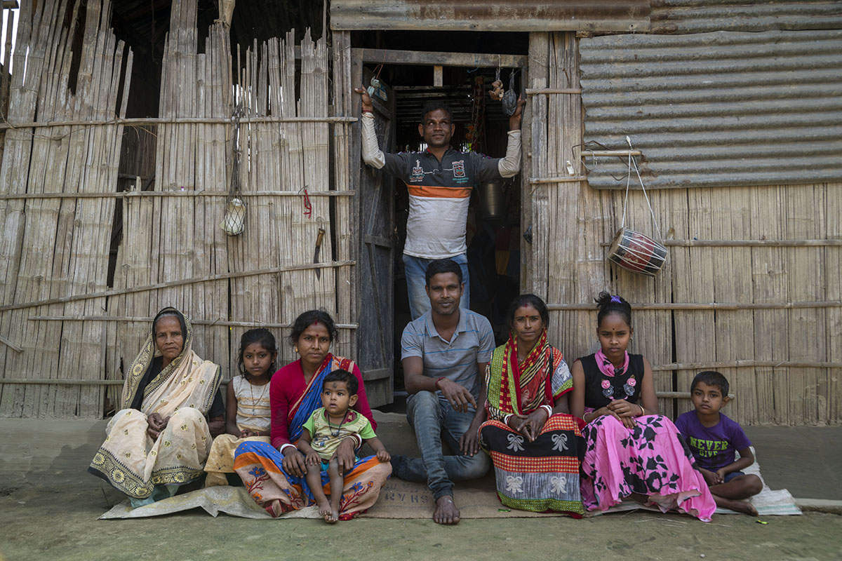 Gobinda is standing in the open doorway of his house, arms raised and resting against the vertical sides of the entrance. The open door as well as the walls of the house are made of bamboo reapers. Just outside the house, sitting cross-legged in a row are eight members of his extended family. On the wall to the right of the doorway a tin sheet has been fixed and hanging from it by a string is a dholak (drum).