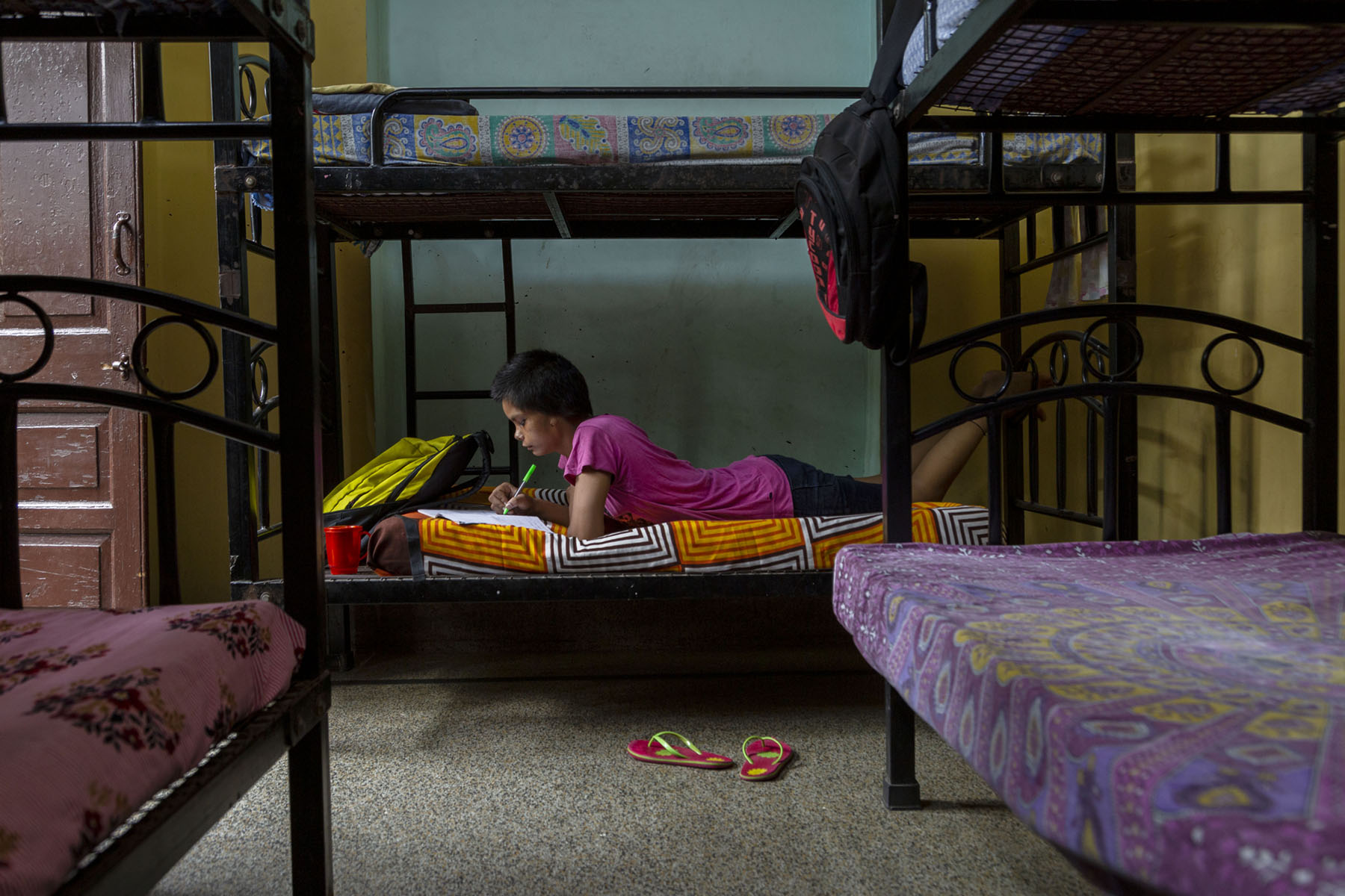 Israna wearing a pink T-shirt and black shorts is stretched out on the lower level of a bunk-bed. The metal frame of the bed is painted black. She is lying on her stomach and writing something in a book with a green pen. There are two bunk-beds on either side perpendicular to her bed. Her mattress is covered with a bedspread in a pattern of orange, black and white squares.