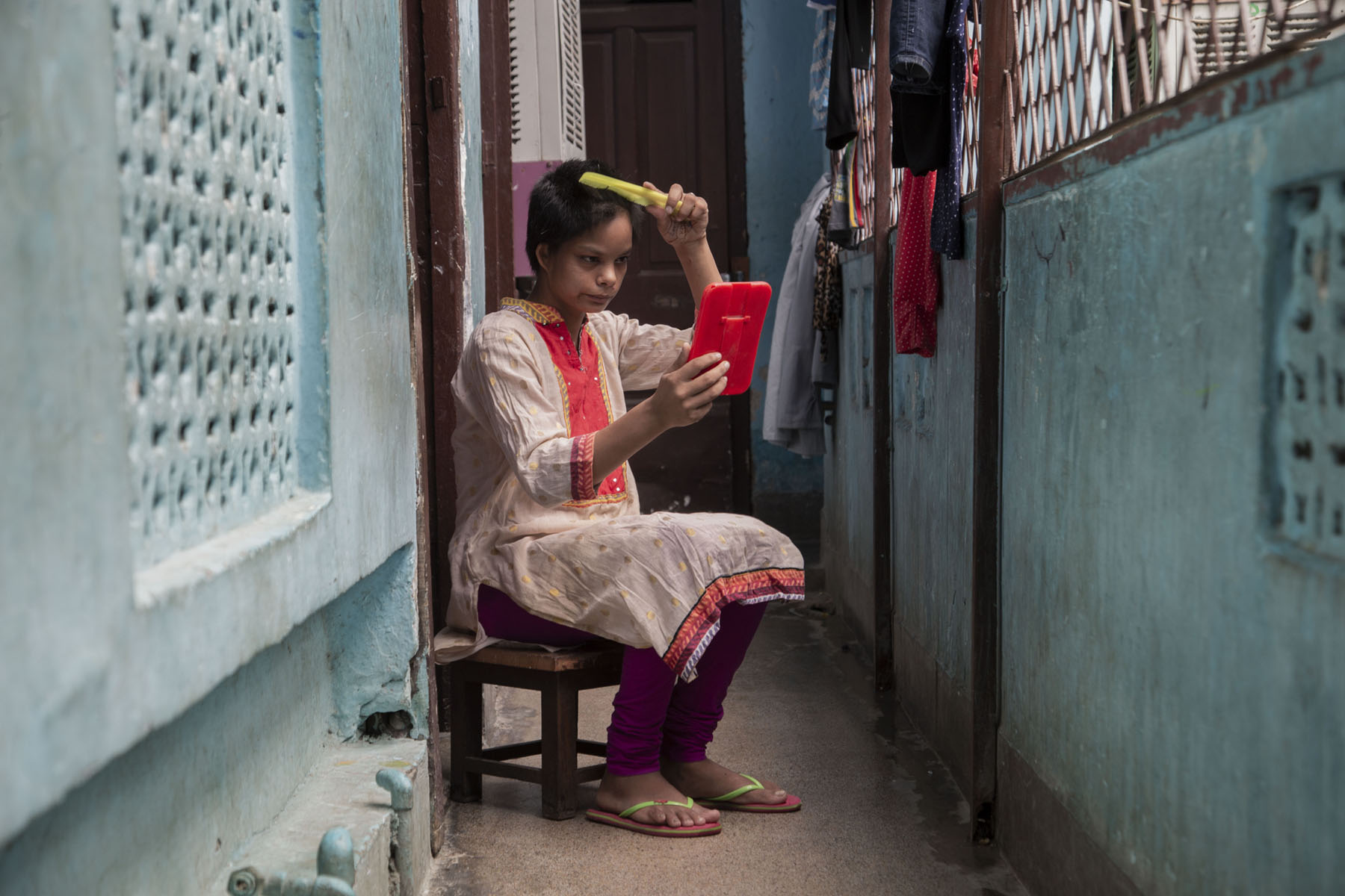 Israna is combing her hair while sitting on a wooden stool placed in a narrow corridor with sky blue walls. She wears a cream kameez and orange salwar, and orange slippers with light green straps. The three-fourth sleeve of the kameez is trimmed with an orange band, and the front of her kameez has an orange panel. She is looking into a hand mirror with an orange back, and holding a yellow comb against the top of her head.
