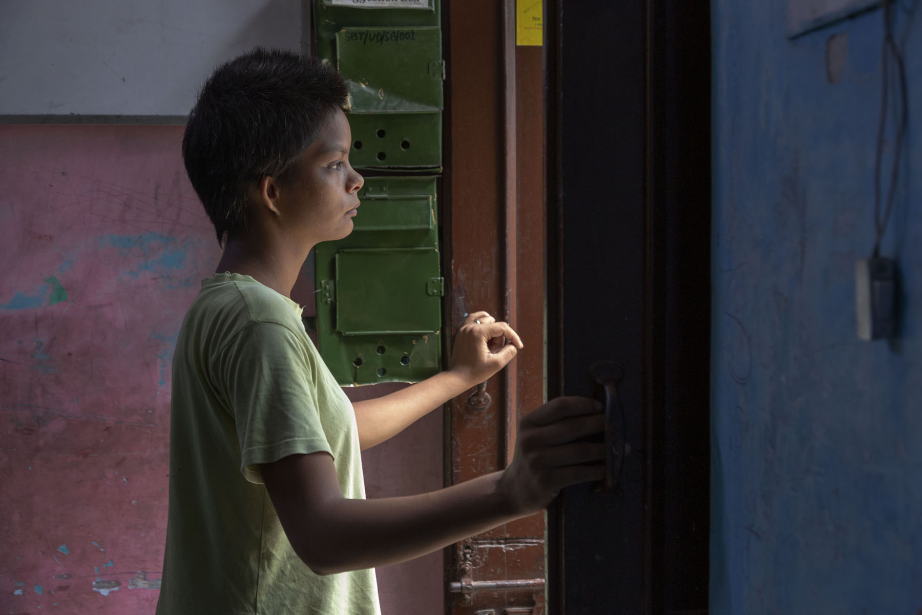 A side shot of Israna in a pista green T-shirt, standing and looking out of a door. She has been photographed in profile, from the waist up. Sunlight is falling on her face and chest. Her hands are raised, holding open the brown wooden shutters of the door.