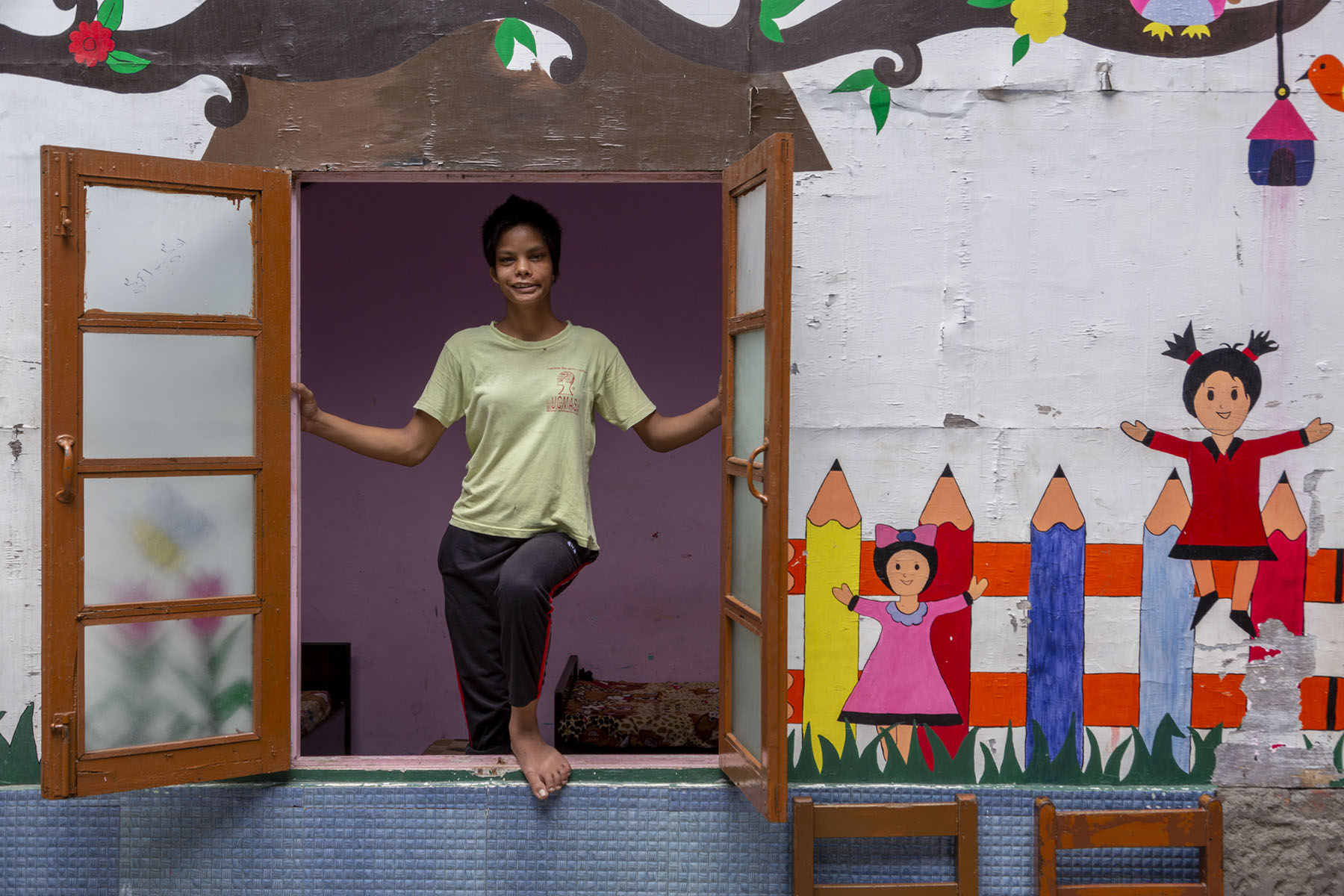 A frontal shot of Israna (18). She has closely cropped straight black hair, and wears a pista green T-shirt and chocolate brown track pants. She is about to step out of a large, open window. Her right leg is behind the window and left leg bent at the knee is resting on top of the window sill. She has raised both hands to grasp either side of the window frame. The two window shutters with glass panes are kept wide open. Colourful murals have been painted on the wall. There are childish drawings of two girls, one wearing a red frock and the other a pink frock. There is a drawing of a row of upright colour pencils in red, yellow, purple, grey and orange. The pencils have three orange horizontal bands running across them, so that the whole image looks like a fence.