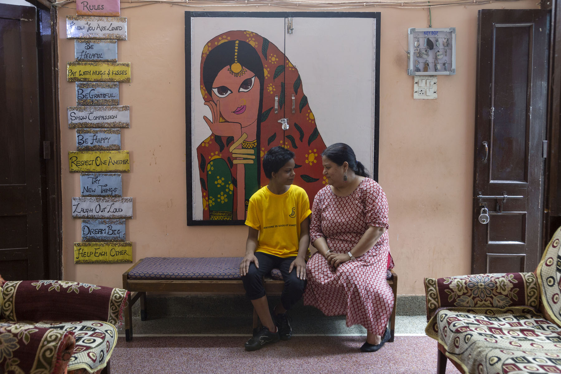 """Israna wearing a yellow T-shirt and knee-high black pants is sitting on a divan next to her Sign language interpreter Shuchi Dasmana (42) who wears a salwar-kameez in a pink and maroon print. A huge painting hangs on the wall behind them. It shows a stylised bust of a woman wearing a green salwar, bangles, golden forehead jewellery (maang tikka) and a red dupatta covering her head. To the left, arranged in a vertical row on the wall are several slogans such as """"Be Helpful"""", """"Respect one another"""", """"Show compassion"""" and """"Laugh out loud"""" handwritten in block letters."""