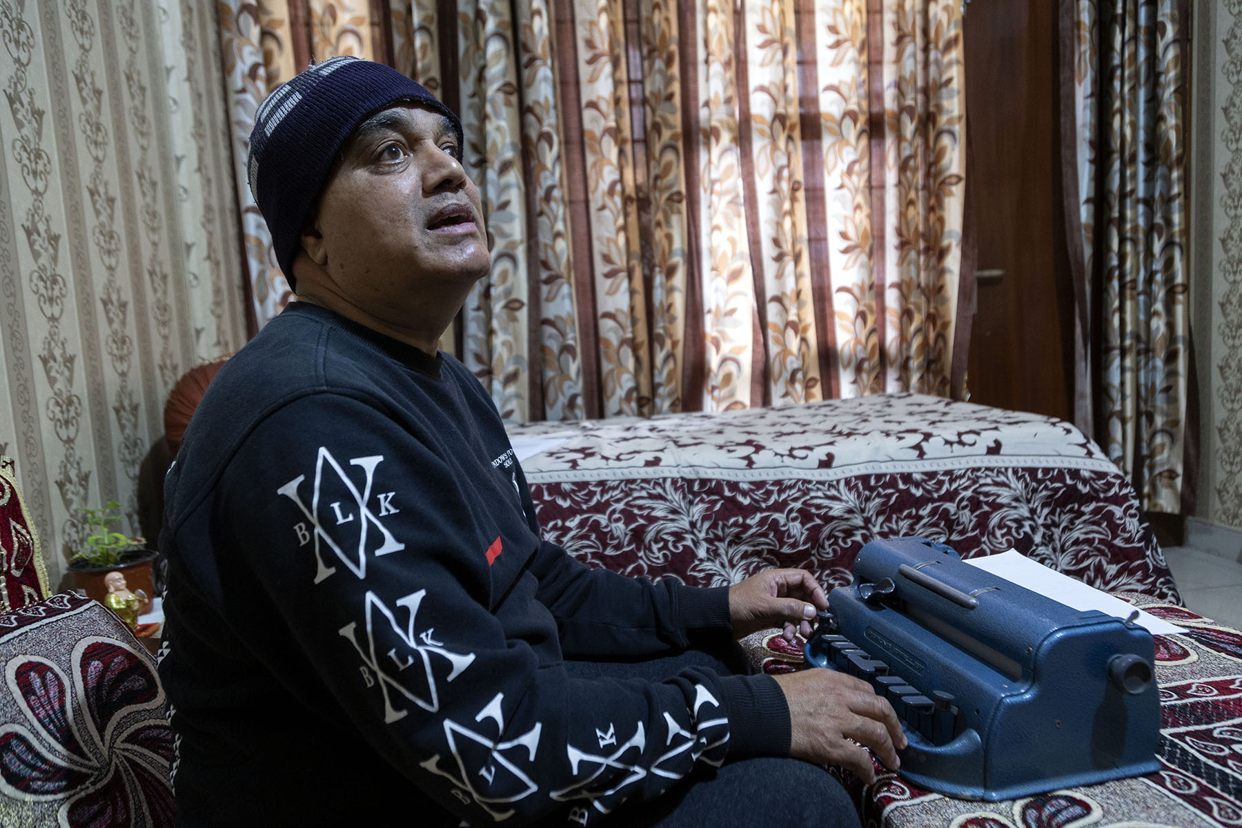 J.S. Jayara in a navy blue sweatshirt and matching woollen cap looking upwards as he sits with his fingers on the keys of a blue Braille typewriter