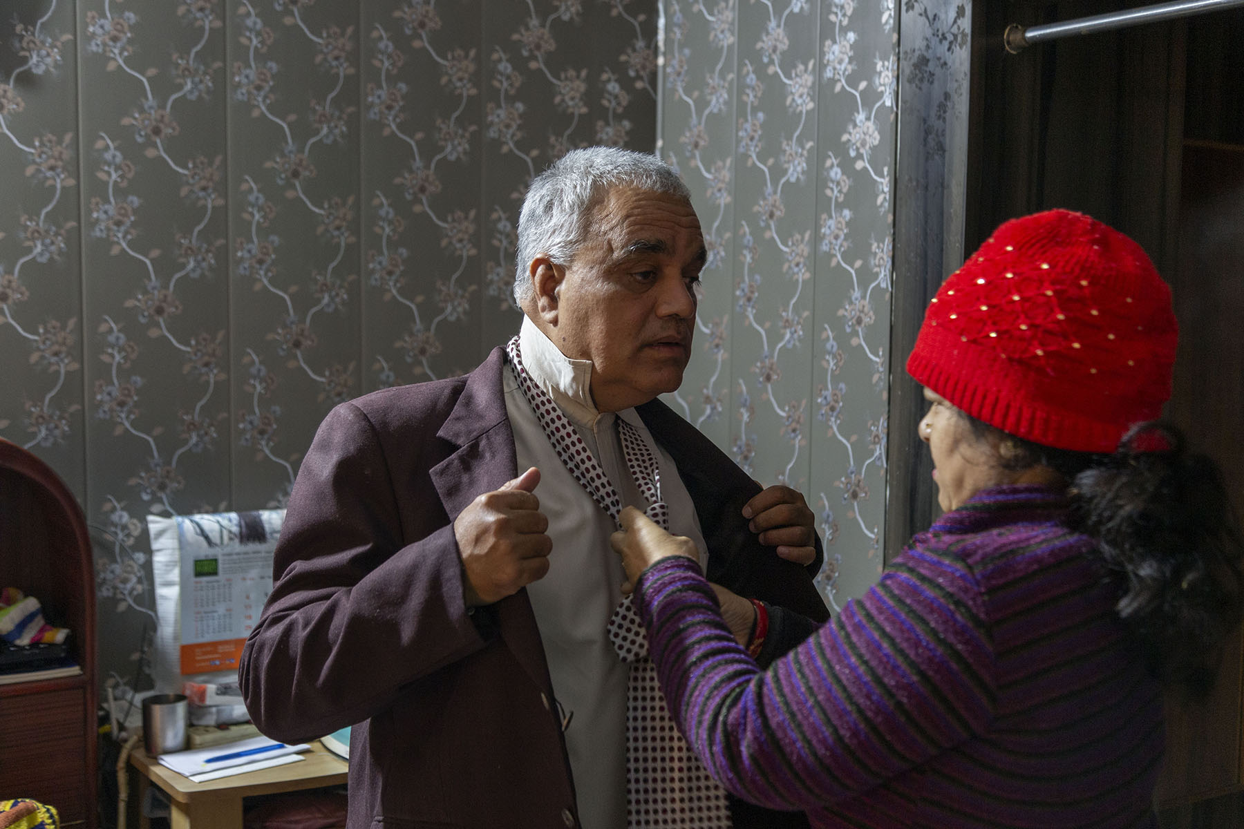 Jayara in a brown coat and shirt with upturned collar standing in front of his wife who is knotting his tie for him