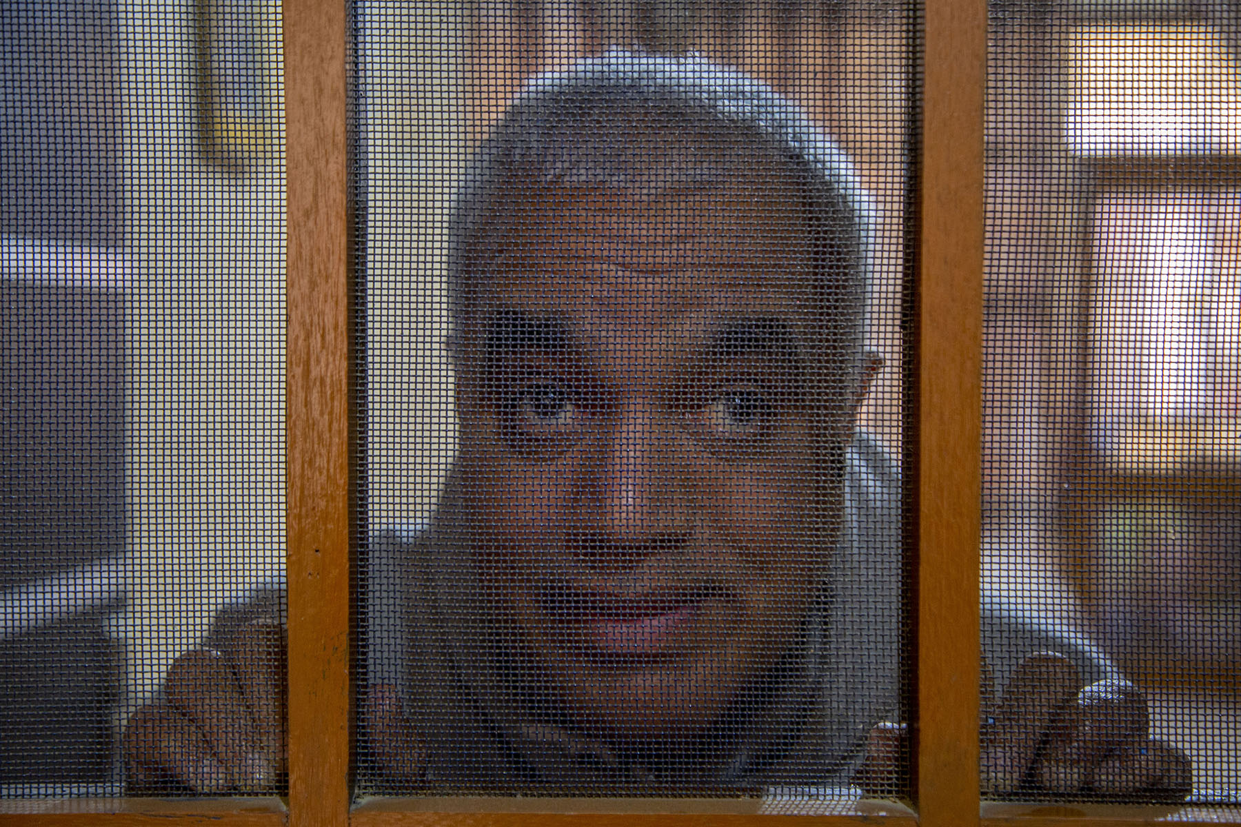 Close-up of Jayara staring from behind a metal mesh door that veils his face and creates a portrait of it with its wooden frame