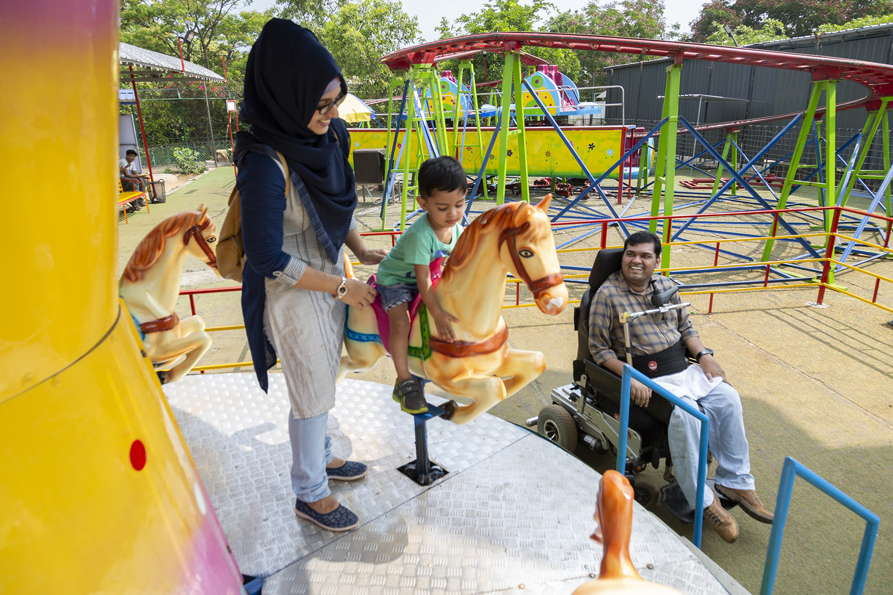 Jesfer, his wife Fathima and two-year-old son Kenzal are in a playground. Fathima and Kenzal have climbed onto a merry-go-round. Fathima wears specs with a black frame, a pale blue and grey churidar-kameez and a black shawl covering her head. She smiles as she supports Kenzal who is seated on one of the peach-coloured carousel horses. Jesfer smiles up at them from his wheelchair on the ground below. In the background is metal play equipment painted red, green, blue and yellow.