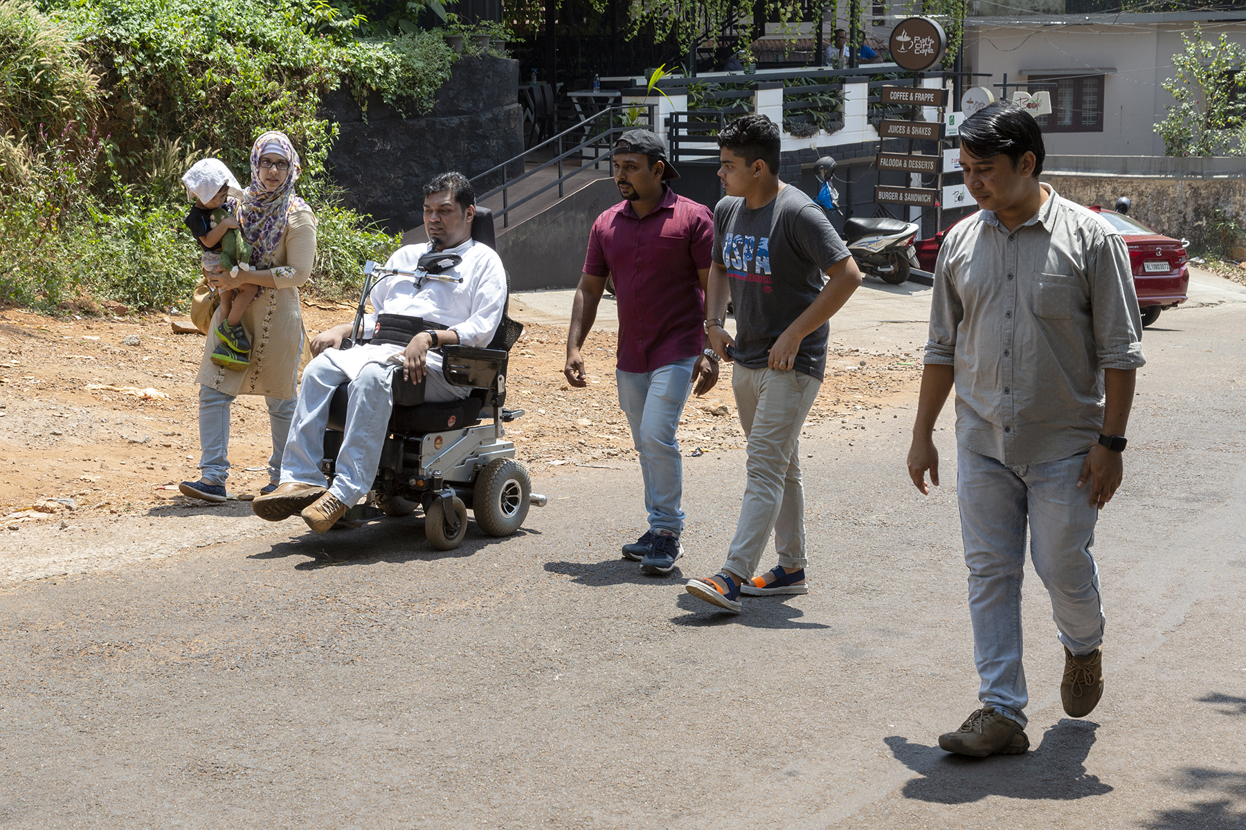 Jesfer in his wheelchair moves along a tarred road with family and friends. Walking beside him is his wife Fathima carrying their son Kenzal in her arms, his nephew and two male friends. Fathima wears a beige kameez and pale blue churidar with a multi-coloured head-covering. A white handkerchief is draped over Kenzal's head to shield him from the sun. Jesfer wears light blue jeans and a pale blue full-sleeve shirt. His nephew wears beige jeans and black T-shirt. Both his friends wear pale blue jeans; one has on a maroon T-shirt and the other, a light grey shirt with sleeves rolled up to the elbow.
