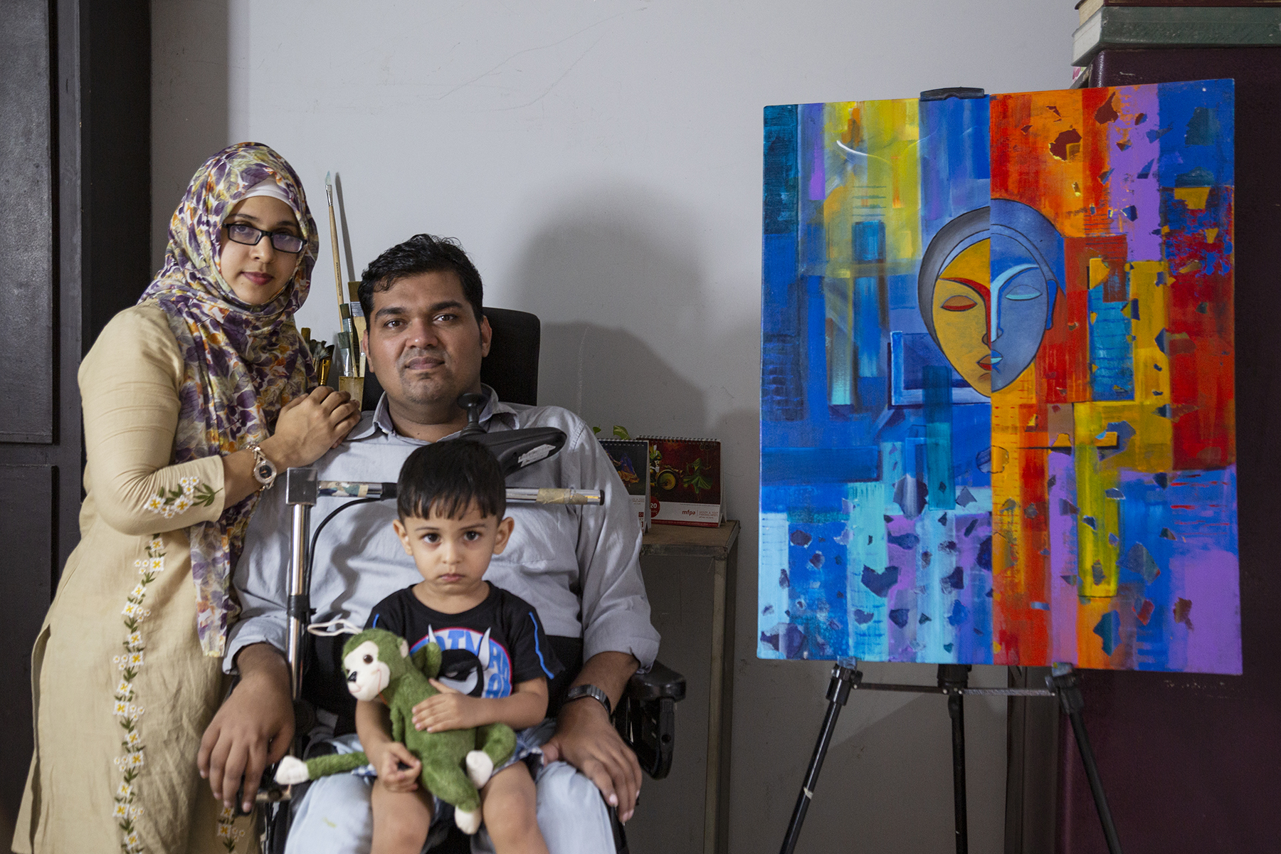Jesfer poses with his wife Fathima PV (31) and son Kenzal Rumi (2) next to his painting put up on an easel. Jesfer wears a pale blue shirt and matching jeans. Kenzal sits on his lap, wearing a black T-shirt and holding a green stuffed monkey. Fathima stands to the left, leaning against Jesfer with her arm resting on his shoulder. She wears specs with a black frame, beige kameez and multi-coloured shawl covering her head. The painting is in bold hues of red, yellow and blue, with a mask-like face in the centre.