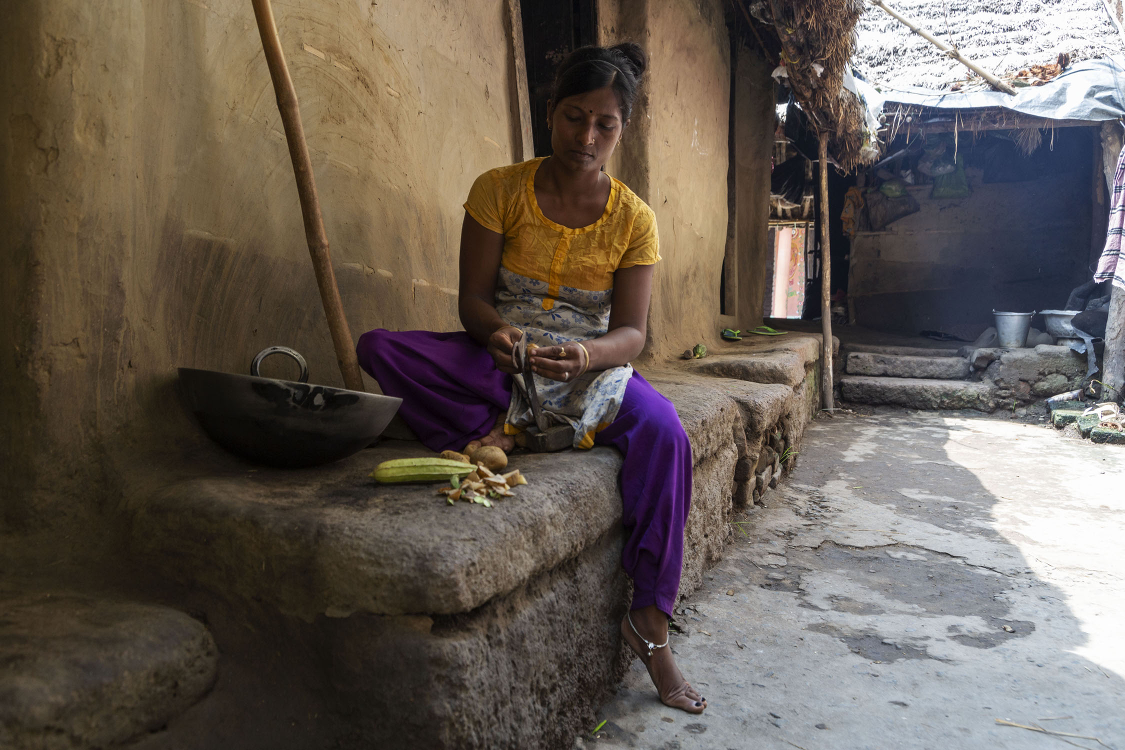 Koushalya sits on the stone ledge that skirts her house. One leg is crossed beneath her and the other is dangling to the ground. She is cutting vegetables with a knife. The outer wall of the house is plastered with mud.