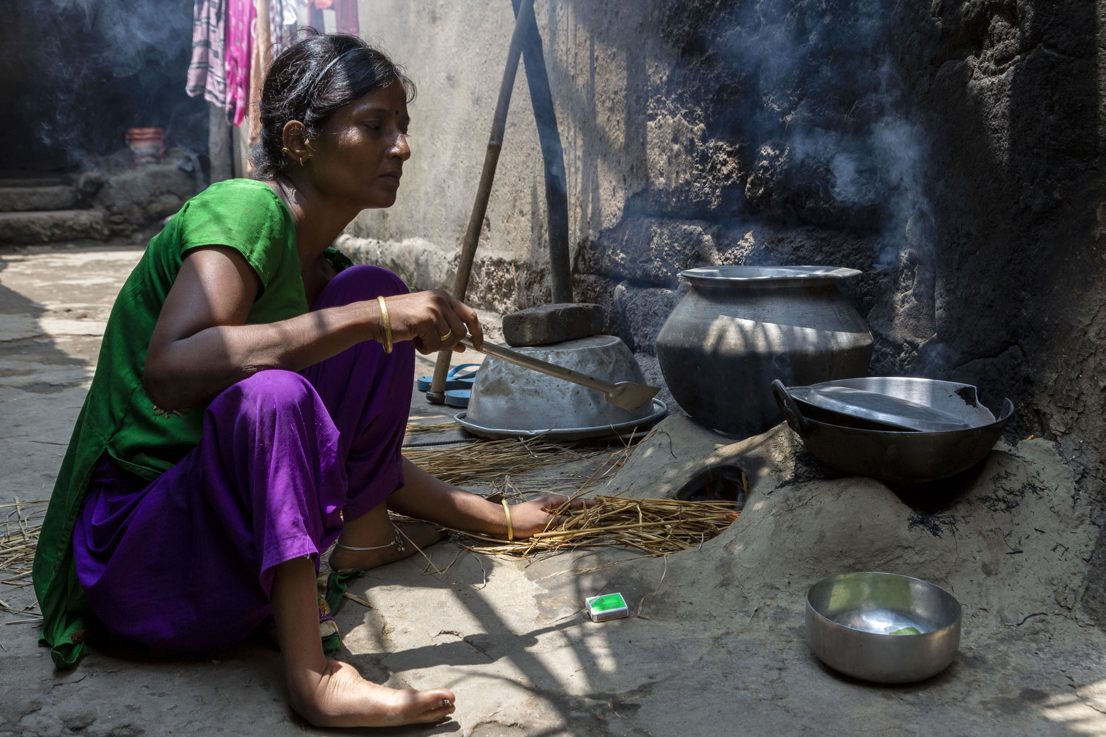 Koushalya in green kameez and purple salwar is squatting outdoors in front of a chulha (earthen stove). She is putting straw into the open mouth of the chulha with her left hand and her right hand holds a steel spatula. An aluminium pot and a kadhai (wok) sit on top of the stove.