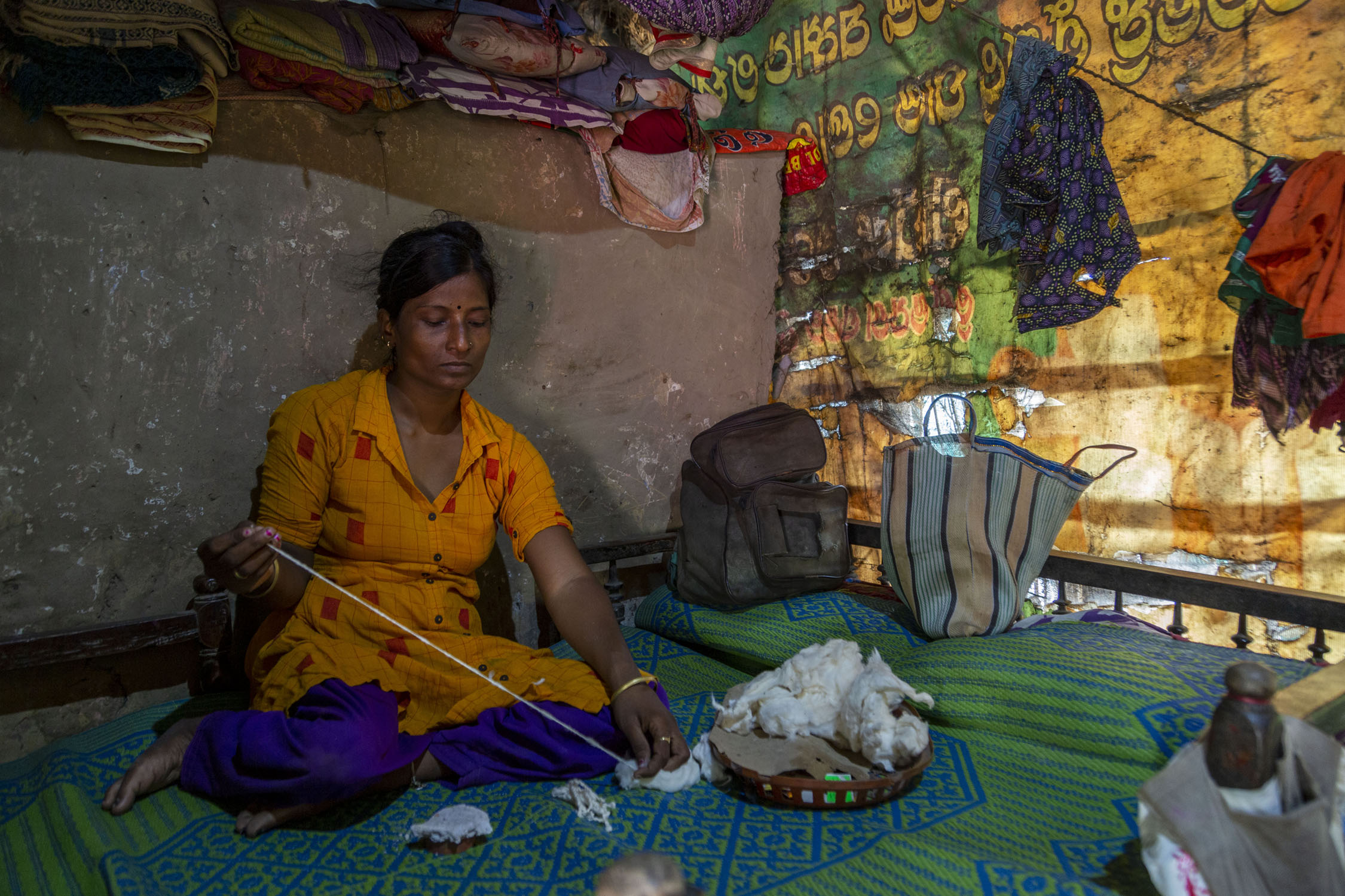Koushalya sits cross-legged on a cot covered with a sheet in a blue and green pattern. A heap of silk-cotton lies on a circular tray next to her. She holds a bunch of cotton in her left hand and with her right hand she is drawing out a thread.
