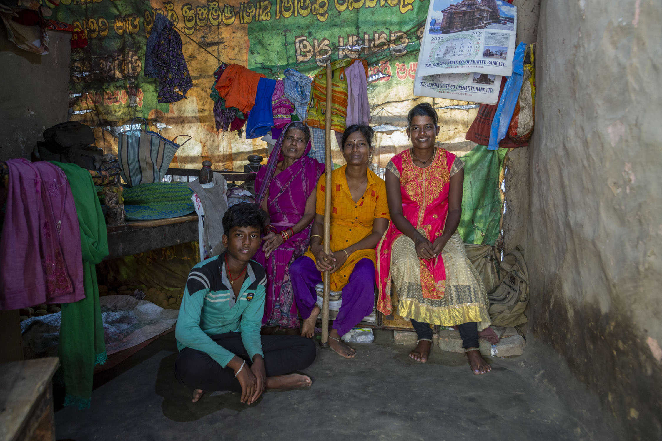 Koushalya poses with members of her family. Sitting cross-legged on the floor is her nephew Kanha Swain (14). Koushalya is seated in between her mother Puni Swain (71) and sister Tunamani Swain (28). Kanha is in a full-sleeved light blue T-shirt and dark trousers. Puni wears a purple sari with her head covered by the pallu. Koushalya wears an orange kameez and purple salwar. Tunamani wears a red and cream kameez and black churidar.