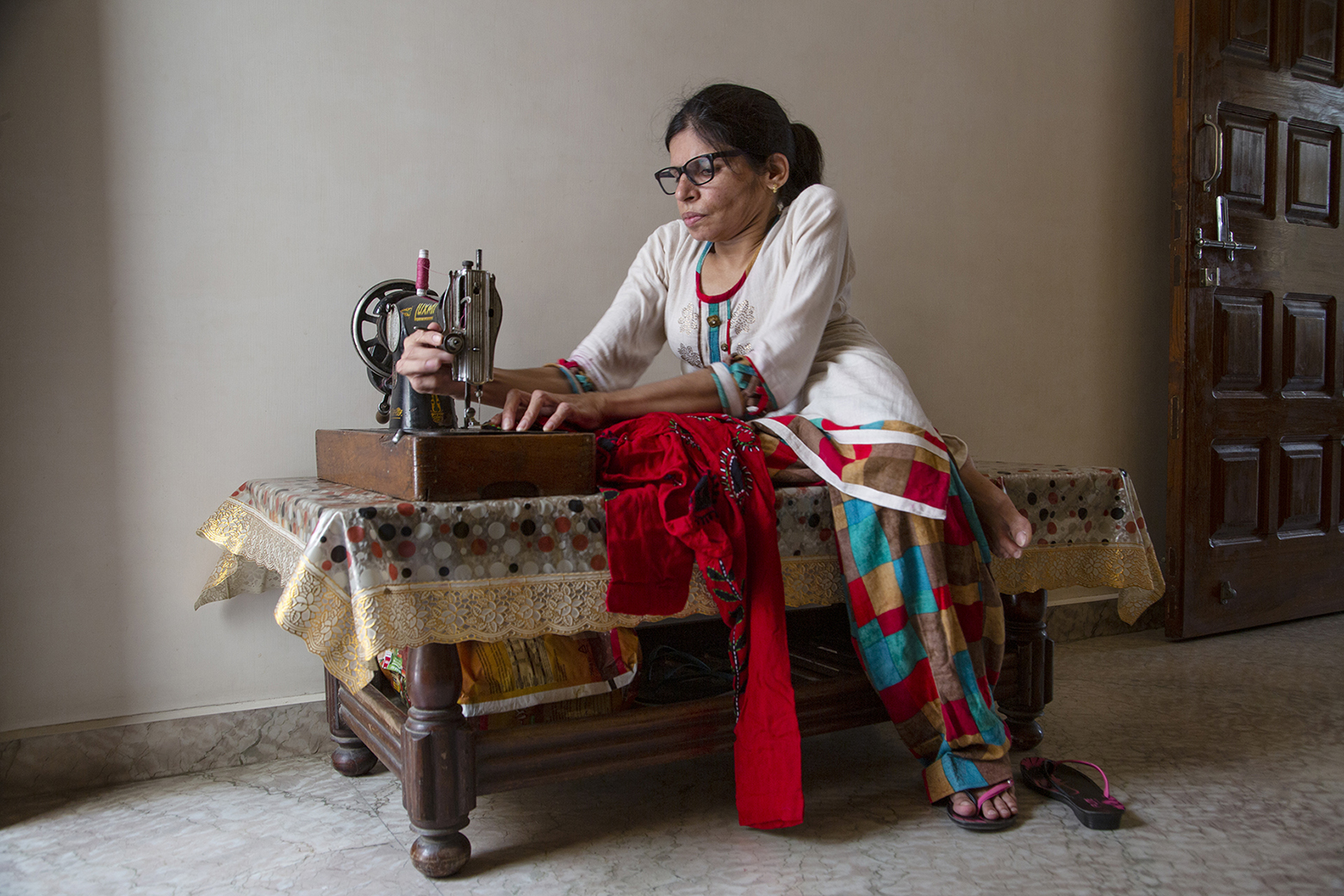 Kavita Mathur is stitching a red kurta on an old-fashioned tabletop sewing machine. The machine is placed on a low, sturdy wooden table. Kavita has specs with thick black frames. Wearing a cream kameez and a salwar in a design of red, blue, mustard and brown checks, she is sitting on the table with right leg folded and left leg touching the ground. She is adjusting the machine with her right hand and placing the cloth beneath the needle with her left hand.